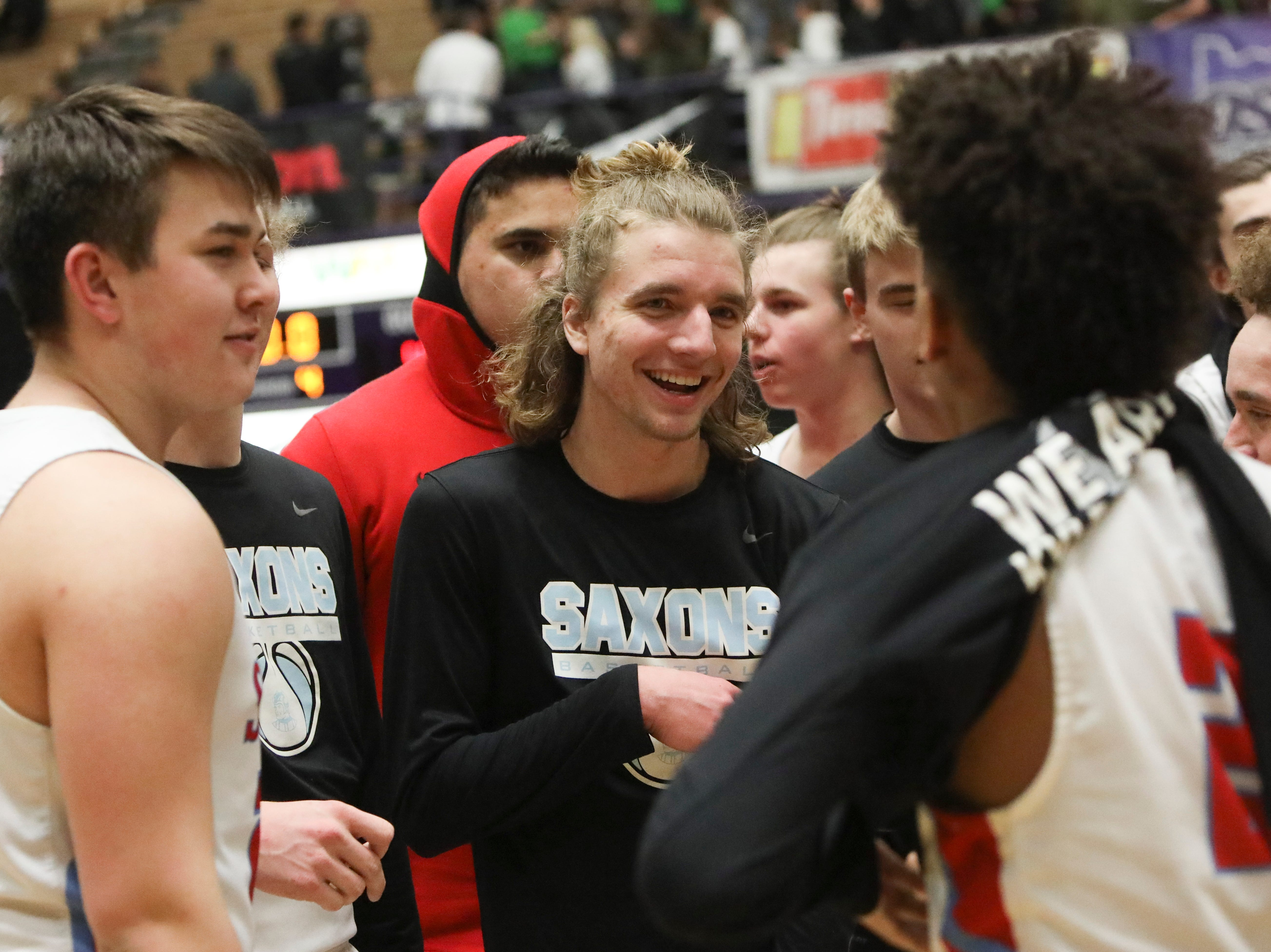 South Salem players celebreate their win over Tigard following the OSAA 6A boys basketball state tournament quarterfinal on Wednesday, March 6 at Chiles Center.