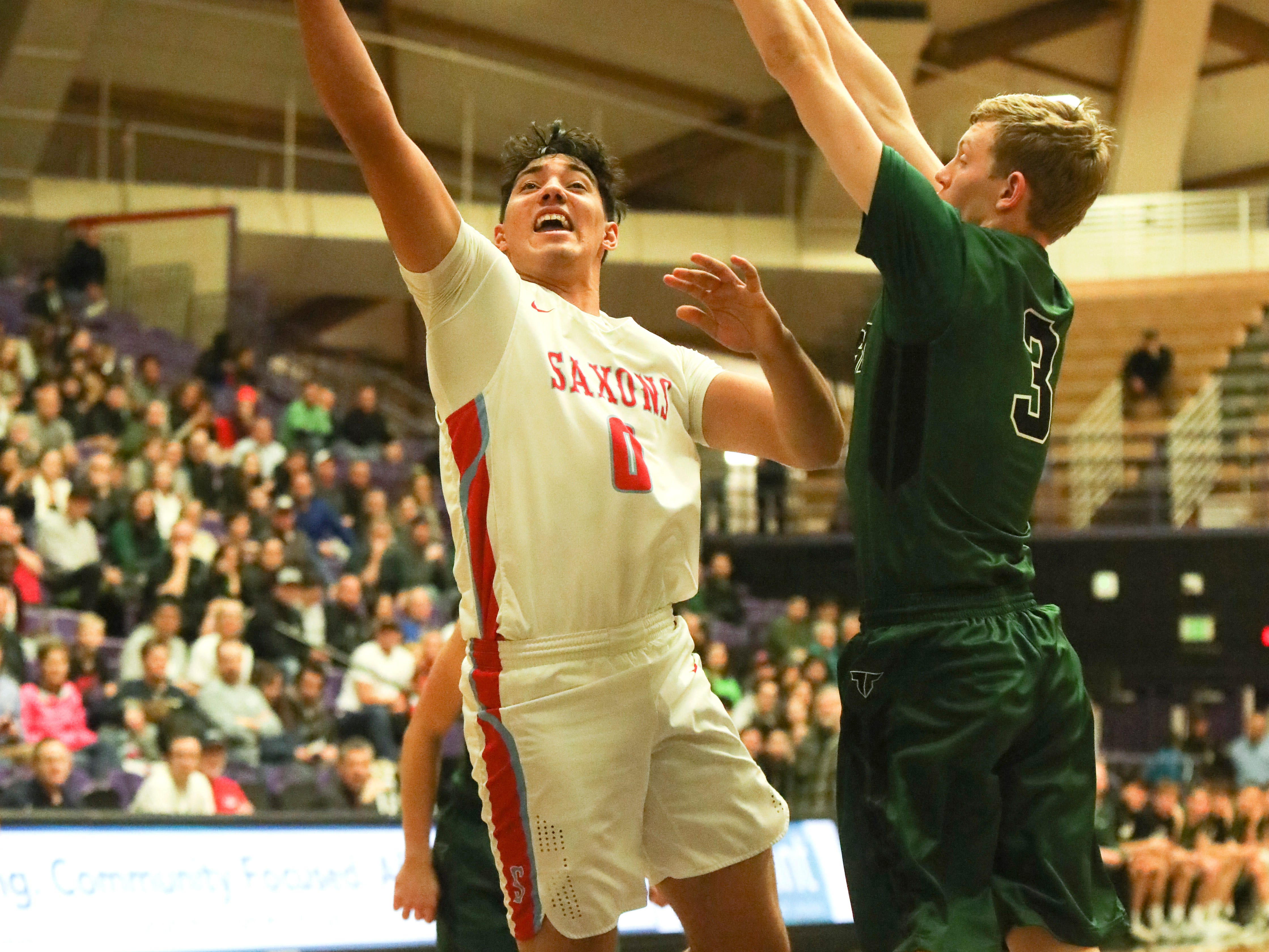 South Salem's Treyden Harris (0) takes a shot past Tigard's Jake Bullard (3) during the OSAA 6A boys basketball state tournament quarterfinal on Wednesday, March 6 at Chiles Center.