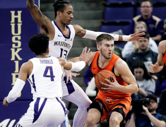 Oregon State forward Tres Tinkle, right, looks to pass around the defense of Washington guard Matisse Thybulle (4) and forward Hameir Wright (13).