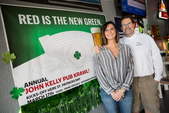 Hannah Kelly, owner of Lucky's pub, and her father Terry Kelly stand in front of the John J. Kelly Pub Krawl promotion sign at Lucky's Pub in Salem on Thursday, Mach 7, 2019.