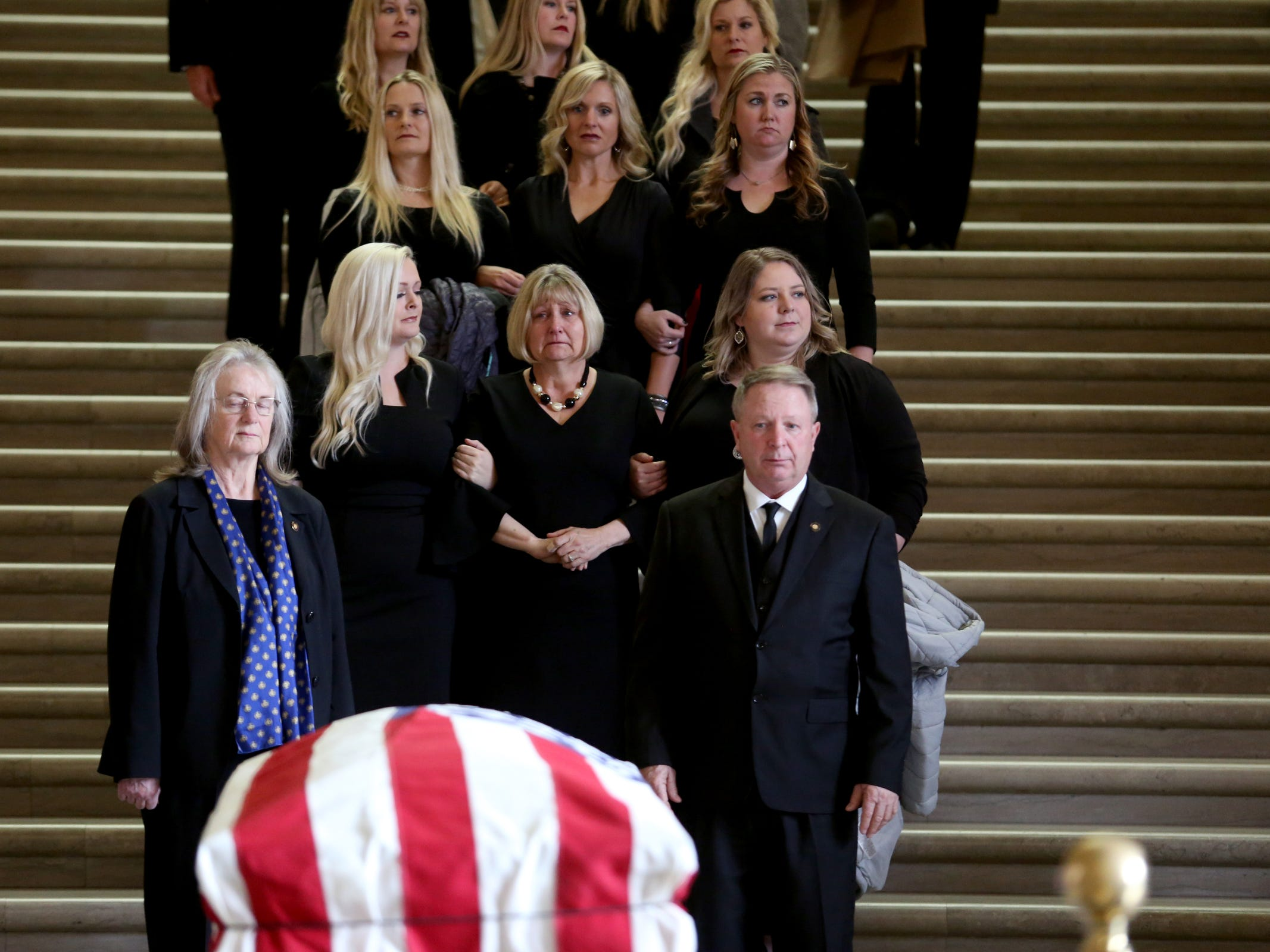 Cathy Richardson is surrounded by family and friends as they exit the Oregon State Capitol during the state funeral for her husband, Secretary of State Dennis Richardson, in Salem on Wednesday, March 6, 2019.