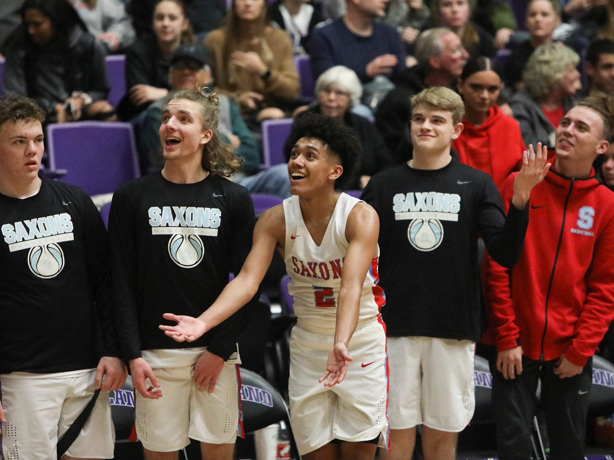 South Salem players try to pump up the student section during the OSAA 6A boys basketball state tournament quarterfinal against Tigard on Wednesday, March 6 at Chiles Center.