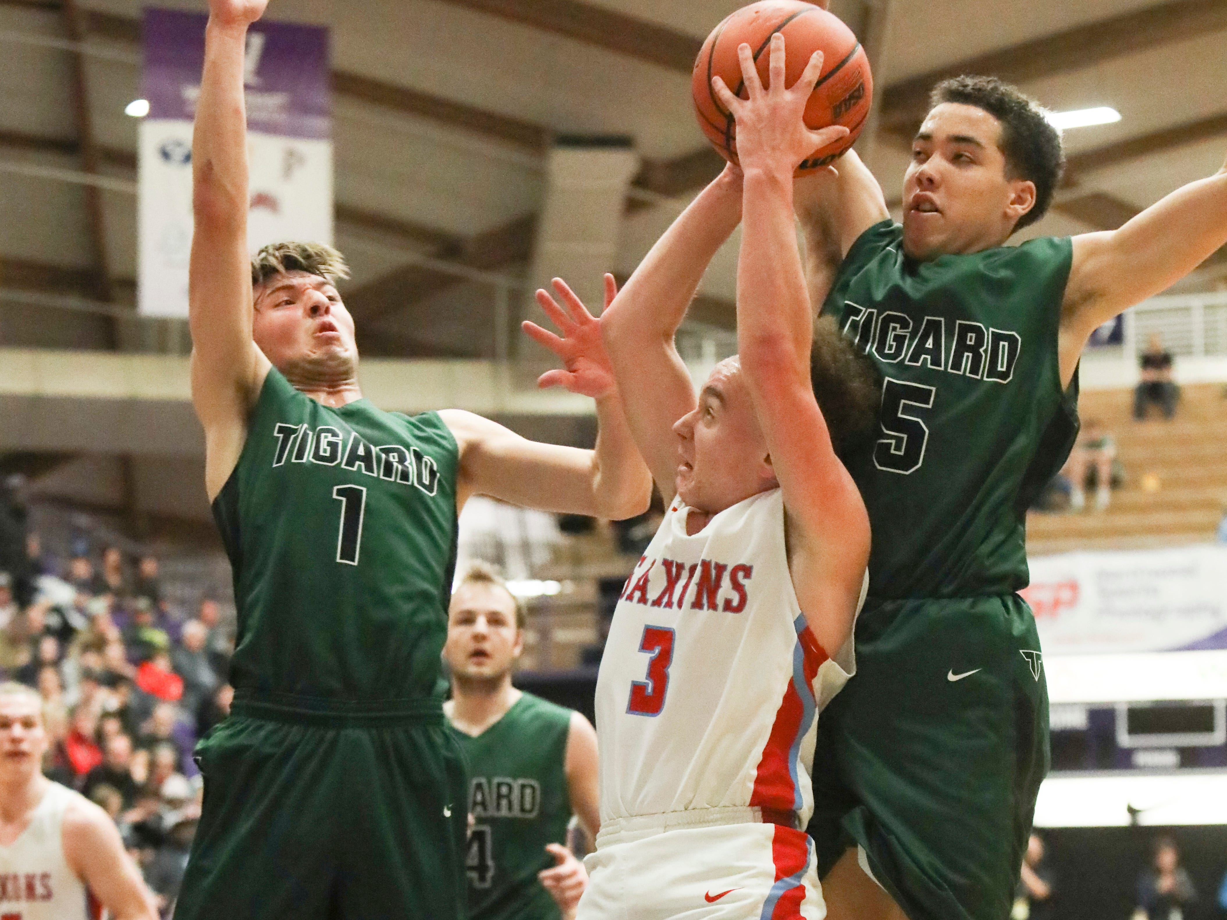 South Salem's Trey Galbraith (3) tries to shoot through Tigard's Diego Lopez (1) and Drew Carter (5) during the OSAA 6A boys basketball state tournament quarterfinal on Wednesday, March 6 at Chiles Center.