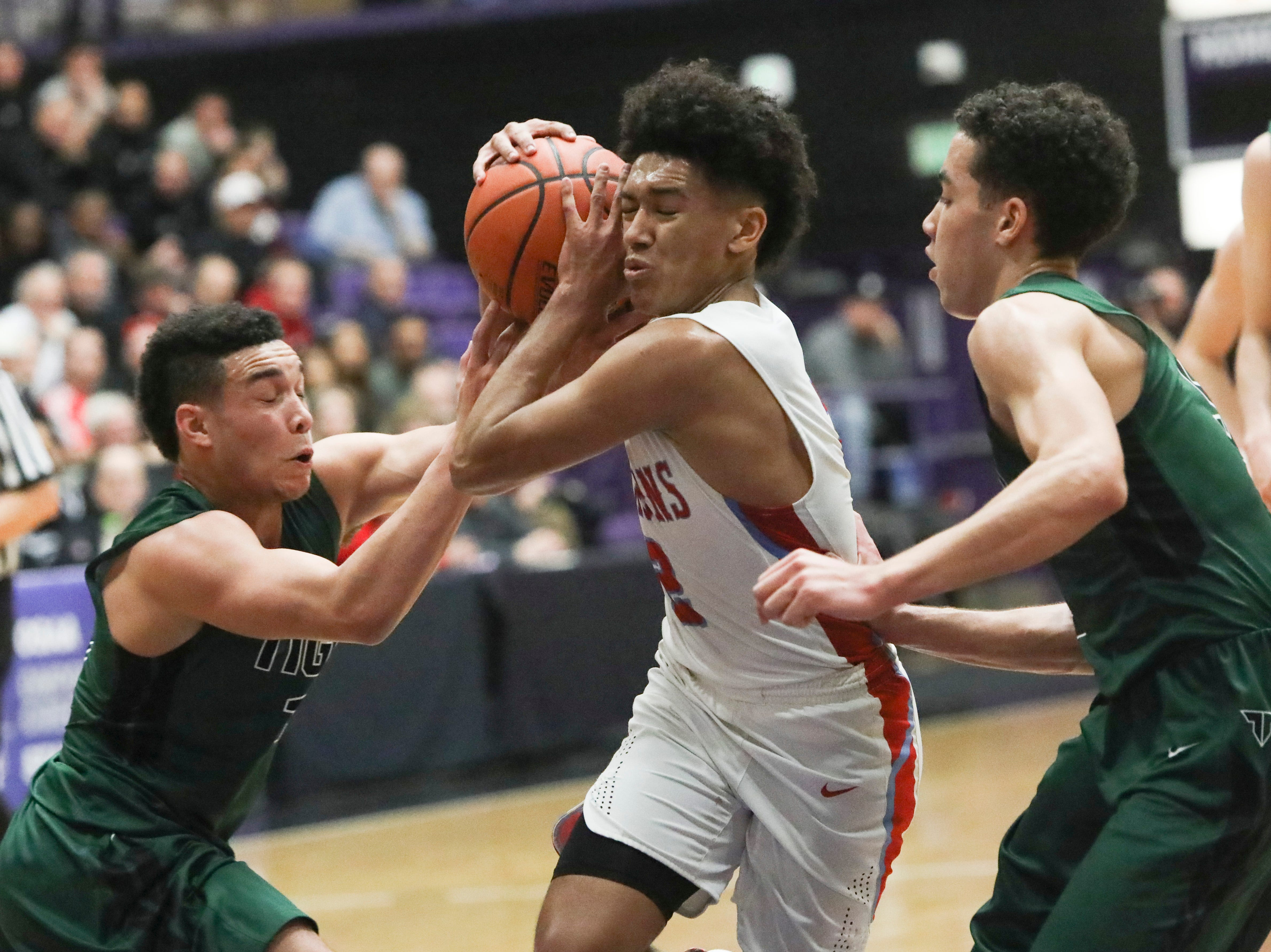 South Salem's Jaden Nielsen-Skinner (2) struggles to keep the ball away from Tigard players during the OSAA 6A boys basketball state tournament quarterfinal on Wednesday, March 6 at Chiles Center.