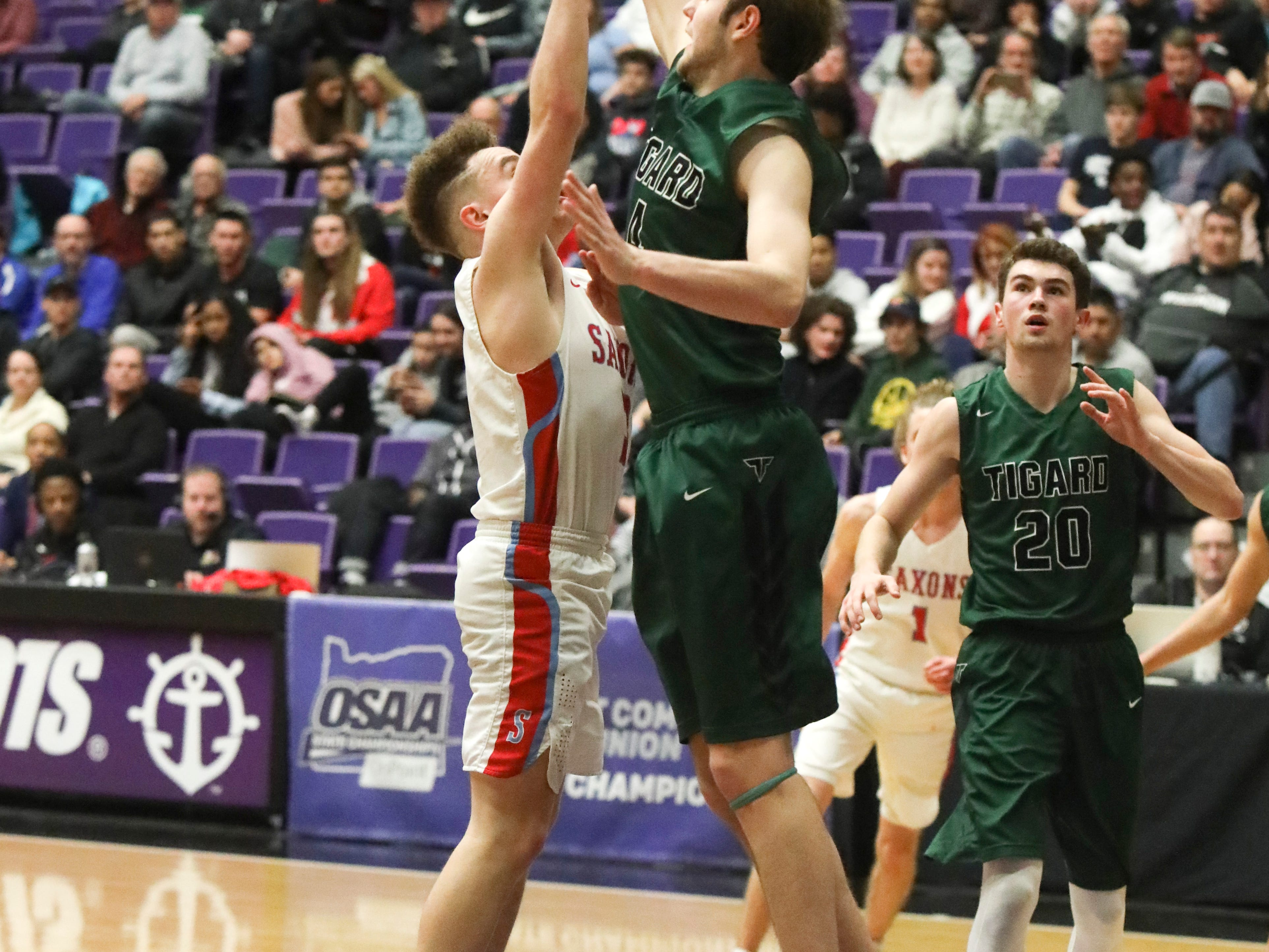 South Salem's Trey Galbraith (3) shoots over Tigard's Stevie Schlabach (4) during the OSAA 6A boys basketball state tournament quarterfinal on Wednesday, March 6 at Chiles Center.