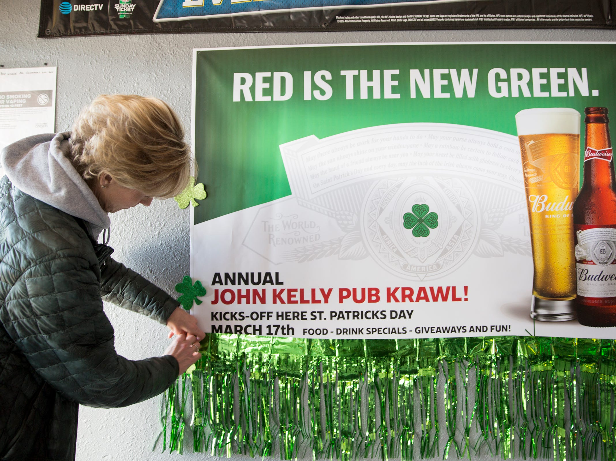 Peggy Kelly fixes the promotional sign and decorations for the annual John J. Kelly Pub Krawl at Lucky's Pub in Salem on Thursday, Mach 7, 2019. The pub crawl will take place on March 17.