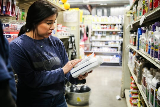 Atalie Jasso reads a label for a customer Wednesday, March 6, 2019, at Palmer Feed.