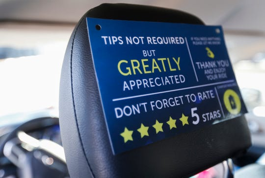 A sign on the back of a headrest in Dorothy Hegelmo's van encourages riders to tip and rate her on the Uber an Lyft apps.