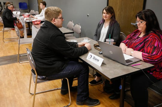 Aaron Siska, of Marshfield, speaks with Diane Manning, right, human resources manager for Russell-Cellular, and Ashley Dale, assistant operations manager, during a hiring event at the Missouri Career Center on Thursday, March 7, 2019.