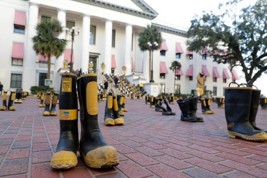 Firefighters and their families from around the state create a display at the Capitol of 500 pairs of boots in honor of firefighters who lost their battle or are battling with cancer caused from smoke inhalation and carcinogens Thursday, March 7, 2019. The state of Florida is one of five states in the country that does not have a bill acknowledging cancer is a job-related illness.