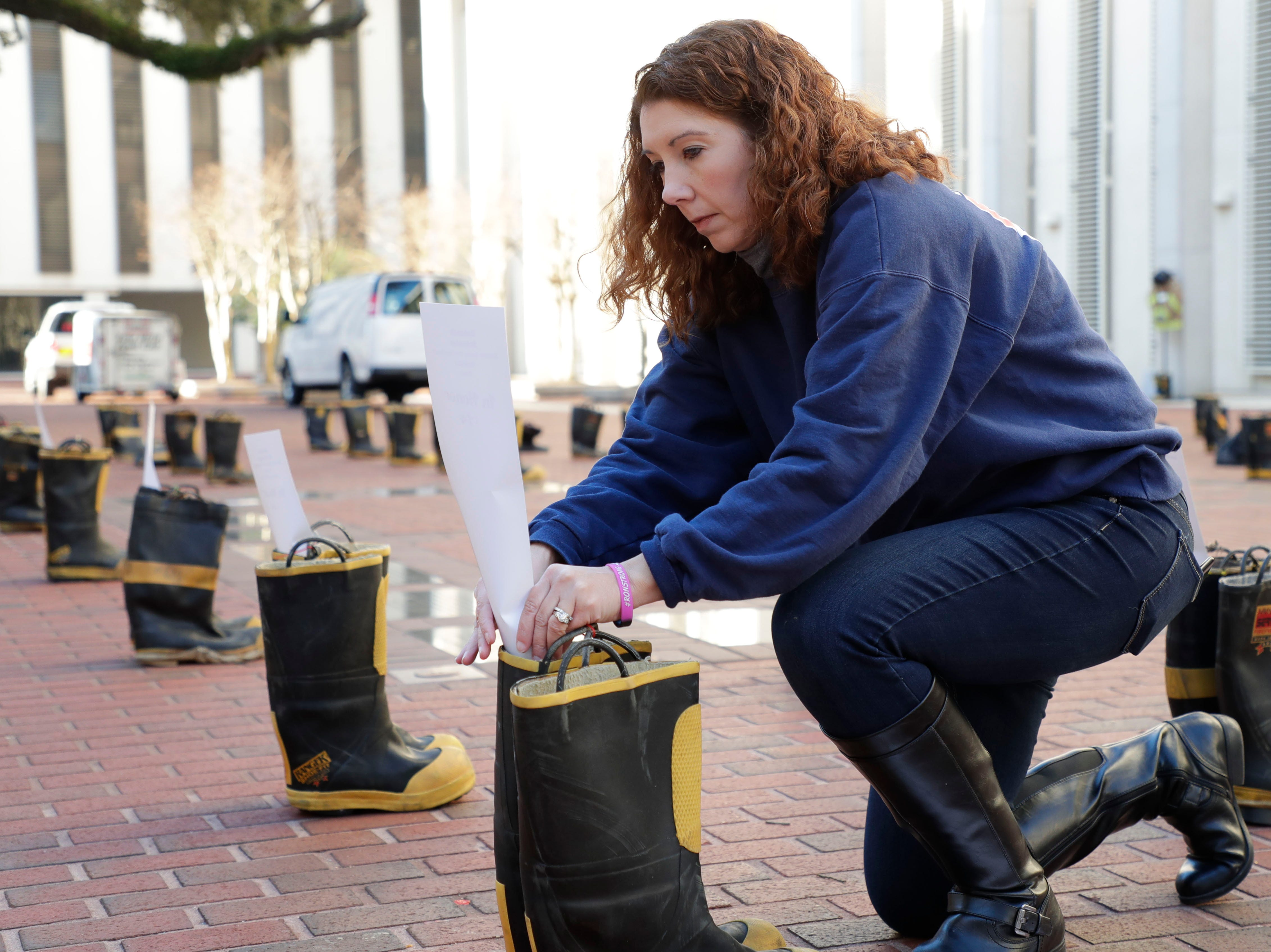 Ashley Rabon, a mother of three who lost her husband who was a firefighter with the Jacksonville Beach Fire Department when he lost his battle to appendix cancer, places a card honoring a fallen firefighter. Firefighters and their families from around the state create a display at the Capitol of 500 pairs of boots in honor of firefighters who lost their battle or are battling with cancer caused from smoke inhalation and carcinogens Thursday, March 7, 2019. The state of Florida is one of five states in the country that does not have a bill acknowledging cancer is a job-related illness.