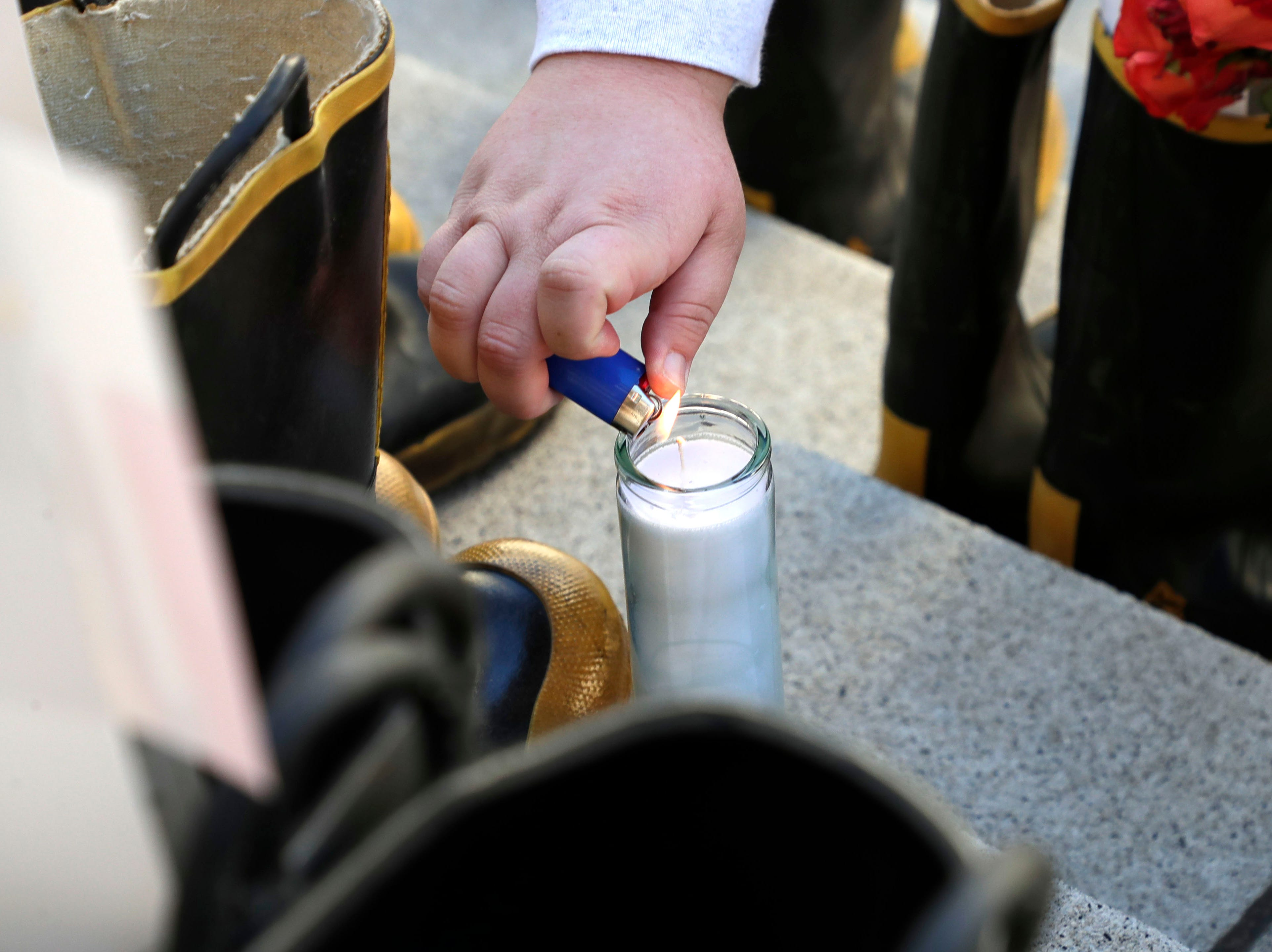 Jaclynn Cusell, a firefighter with Palm Beach County Fire Department, lights a candle to honor her father, Henry Cusell who battled Non-Hodgkins lymphoma. Firefighters and their families from around the state create a display at the Capitol of 500 pairs of boots in honor of firefighters who lost their battle or are battling with cancer caused from smoke inhalation and carcinogens Thursday, March 7, 2019. The state of Florida is one of five states in the country that does not have a bill acknowledging cancer is a job-related illness.