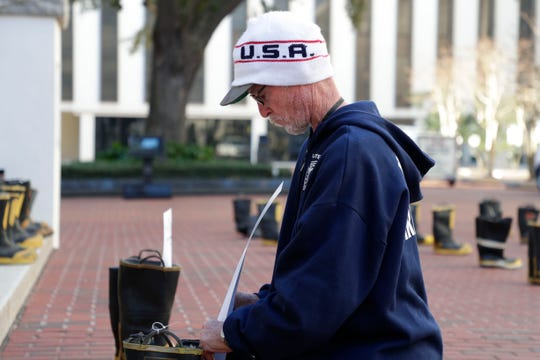 Jay Post, a former Brevard County Fire Department firefighter who is battling throat cancer, places a card honoring a fellow firefighter who lost their battle to cancer. Firefighters and their families from around the state create a display at the Capitol of 500 pairs of boots in honor of firefighters who lost their battle or are battling with cancer caused from smoke inhalation and carcinogens Thursday, March 7, 2019. The state of Florida is one of five states in the country that does not have a bill acknowledging cancer is a job-related illness.