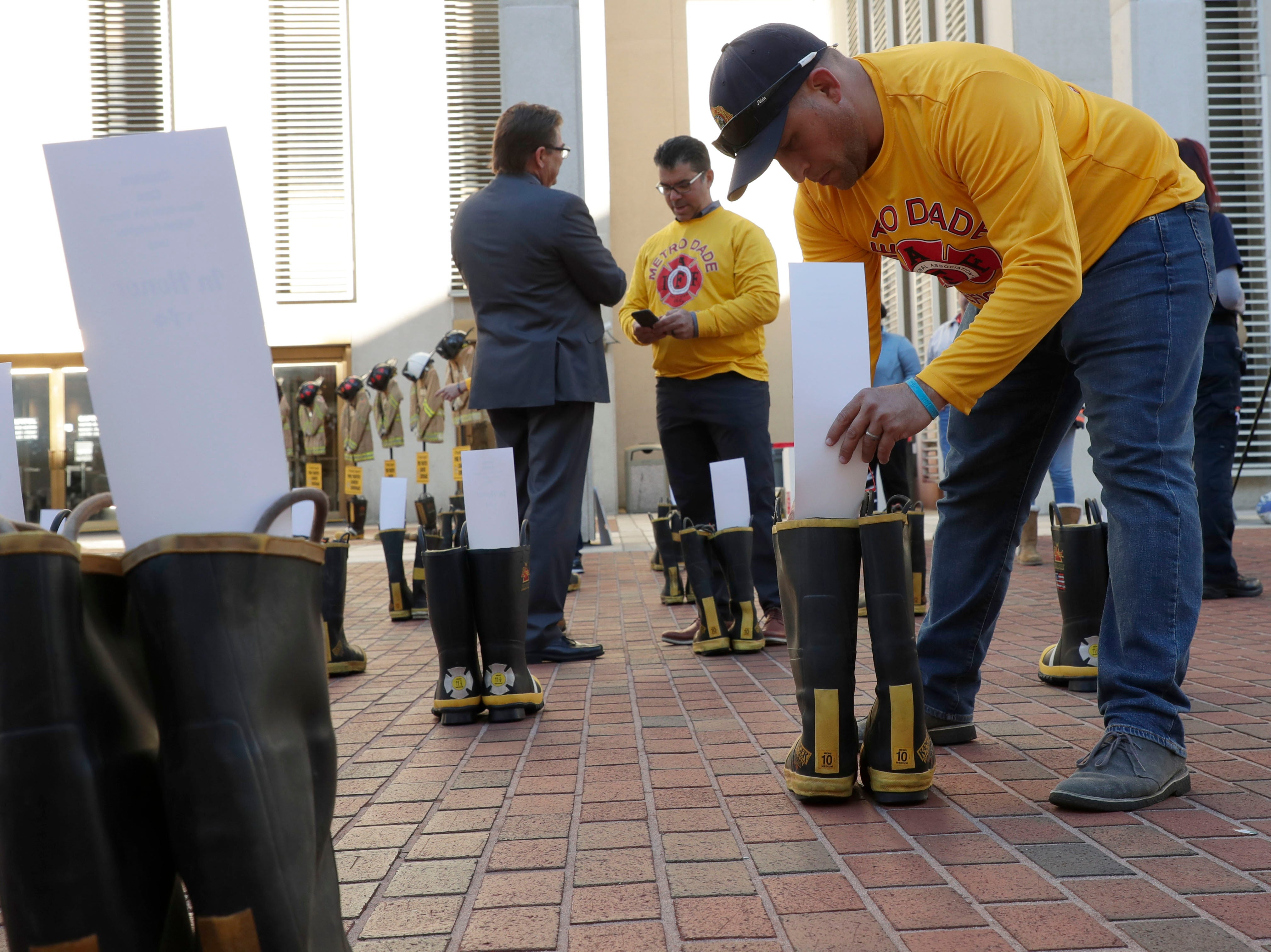 Felipe Lay, a firefighter with Miami-Dade Local 1403, places a card honoring a firefighter battling cancer in a boot. Firefighters and their families from around the state create a display at the Capitol of 500 pairs of boots in honor of firefighters who lost their battle or are battling with cancer caused from smoke inhalation and carcinogens Thursday, March 7, 2019. The state of Florida is one of five states in the country that does not have a bill acknowledging cancer is a job-related illness.