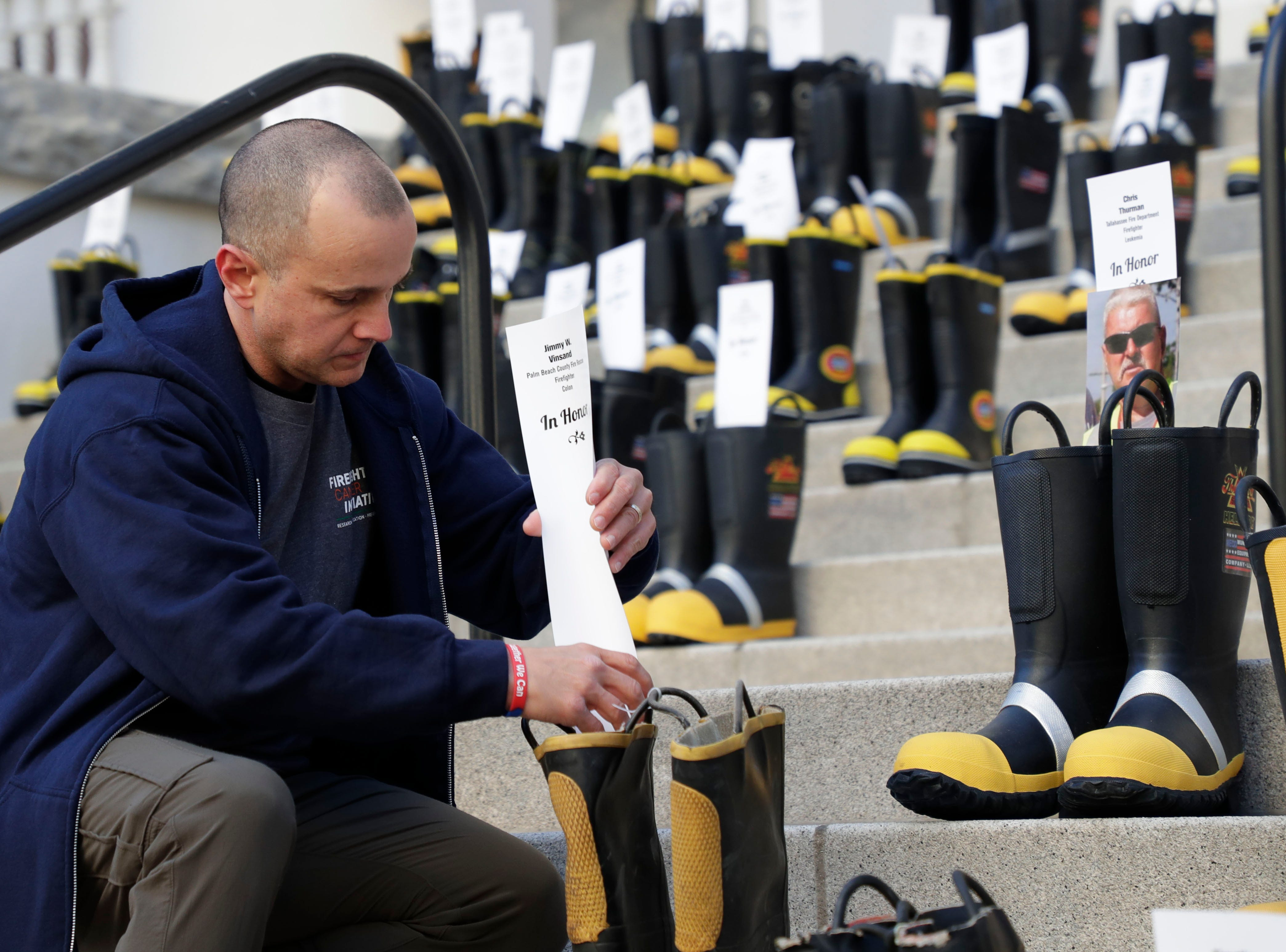 Bert Vergara, a firefighter with Osceola County Fire Rescue, places a card honoring a firefighter who lost their battle with cancer. Firefighters and their families from around the state create a display at the Capitol of 500 pairs of boots in honor of firefighters who lost their battle or are battling with cancer caused from smoke inhalation and carcinogens Thursday, March 7, 2019. The state of Florida is one of five states in the country that does not have a bill acknowledging cancer is a job-related illness.