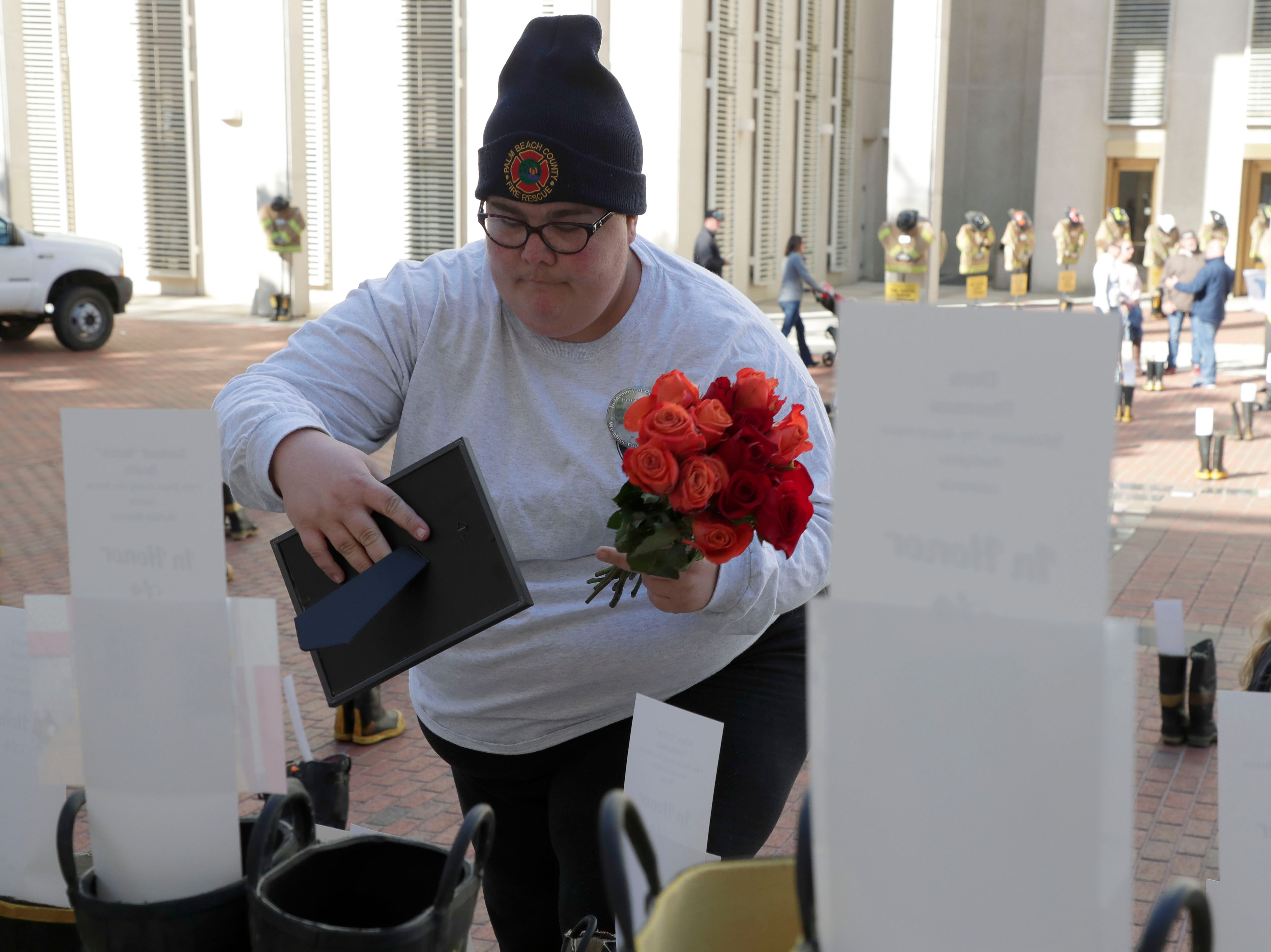 Jaclynn Cusell, a firefighter with Palm Beach County Fire Department, places a framed photo and flowers with a pair of boots honoring her father, Henry Cusell who battled Non-Hodgkins lymphoma. Firefighters and their families from around the state create a display at the Capitol of 500 pairs of boots in honor of firefighters who lost their battle or are battling with cancer caused from smoke inhalation and carcinogens Thursday, March 7, 2019. The state of Florida is one of five states in the country that does not have a bill acknowledging cancer is a job-related illness.