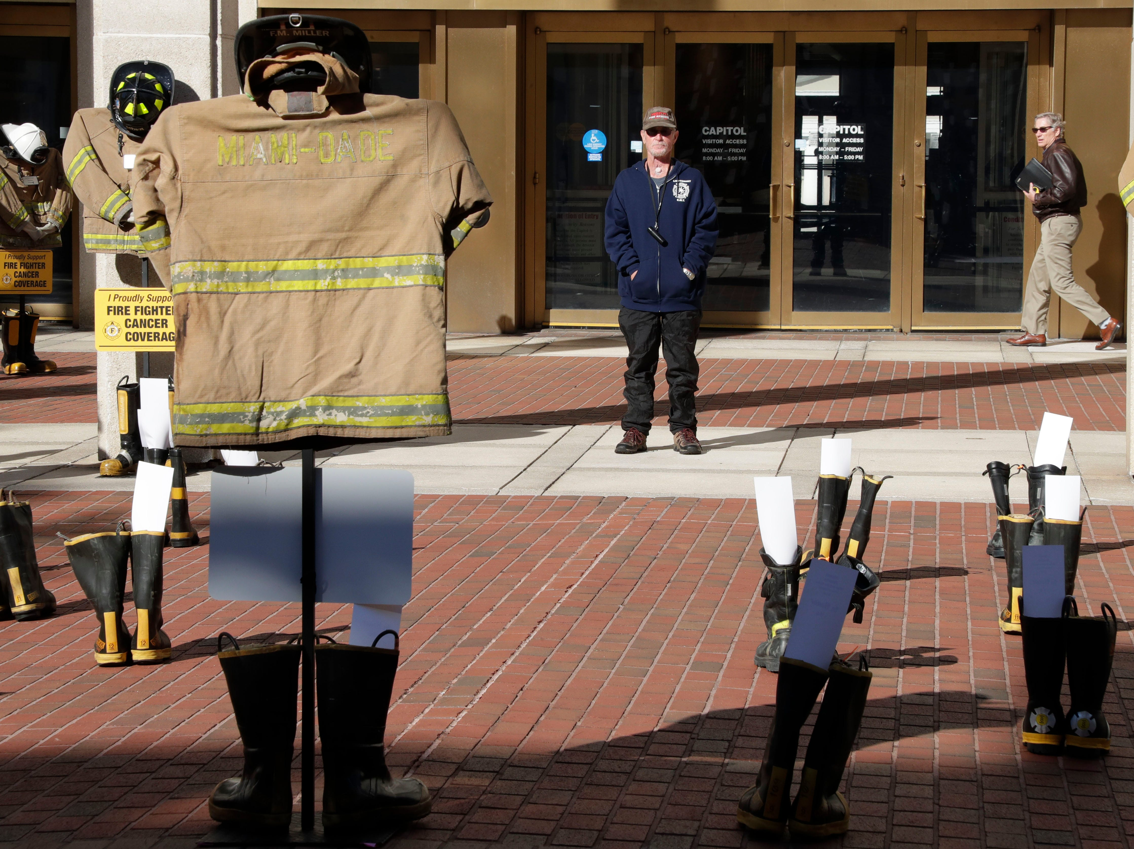 Jay Post, a former firefighter who is now battling throat cancer, takes in the final display created that morning. Firefighters and their families from around the state create a display at the Capitol of 500 pairs of boots in honor of firefighters who lost their battle or are battling with cancer caused from smoke inhalation and carcinogens Thursday, March 7, 2019. The state of Florida is one of five states in the country that does not have a bill acknowledging cancer is a job-related illness.