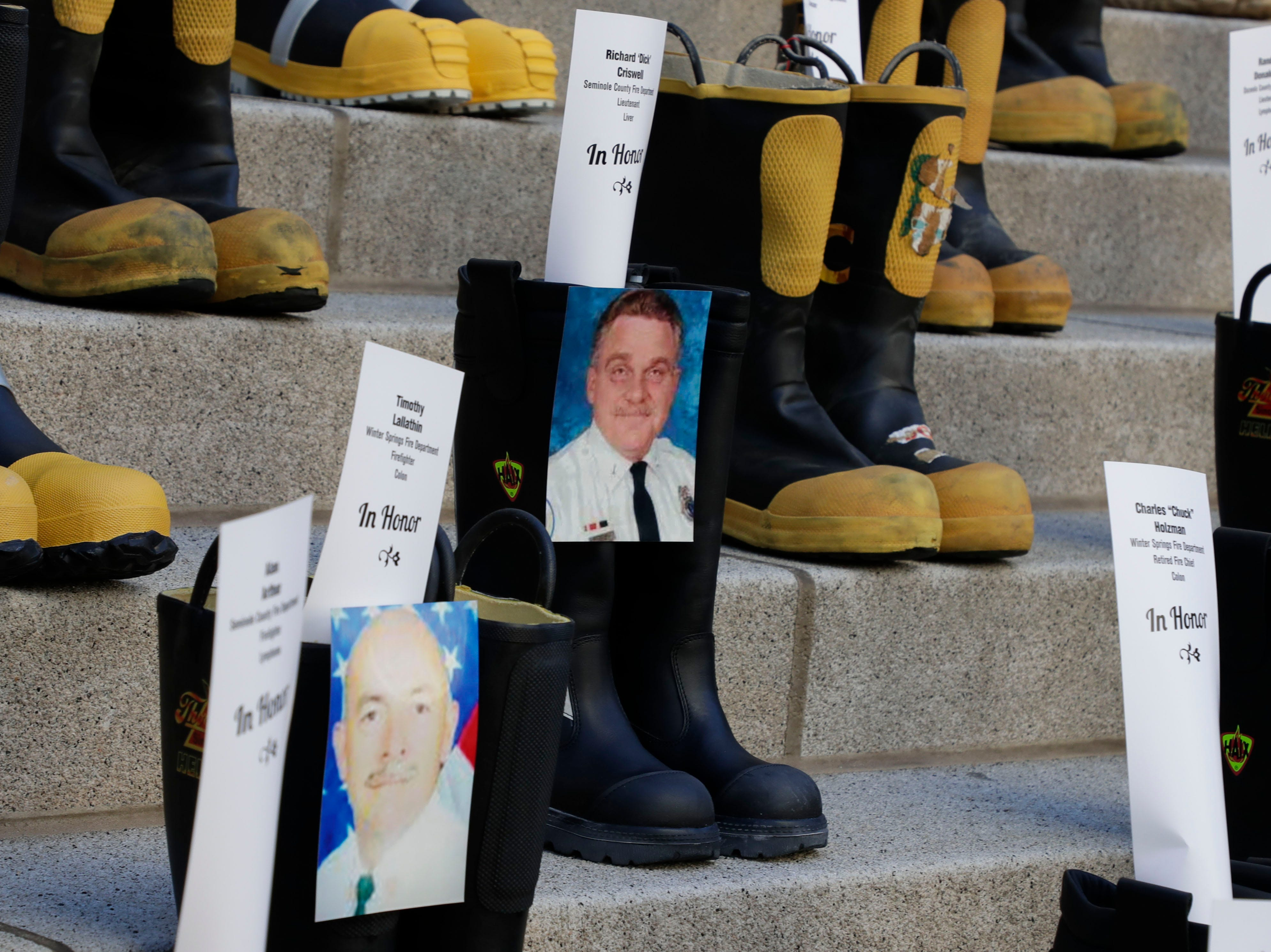 Photos are taped to boots honoring firefighters who battled cancer. Firefighters and their families from around the state create a display at the Capitol of 500 pairs of boots in honor of firefighters who lost their battle or are battling with cancer caused from smoke inhalation and carcinogens Thursday, March 7, 2019. The state of Florida is one of five states in the country that does not have a bill acknowledging cancer is a job-related illness.