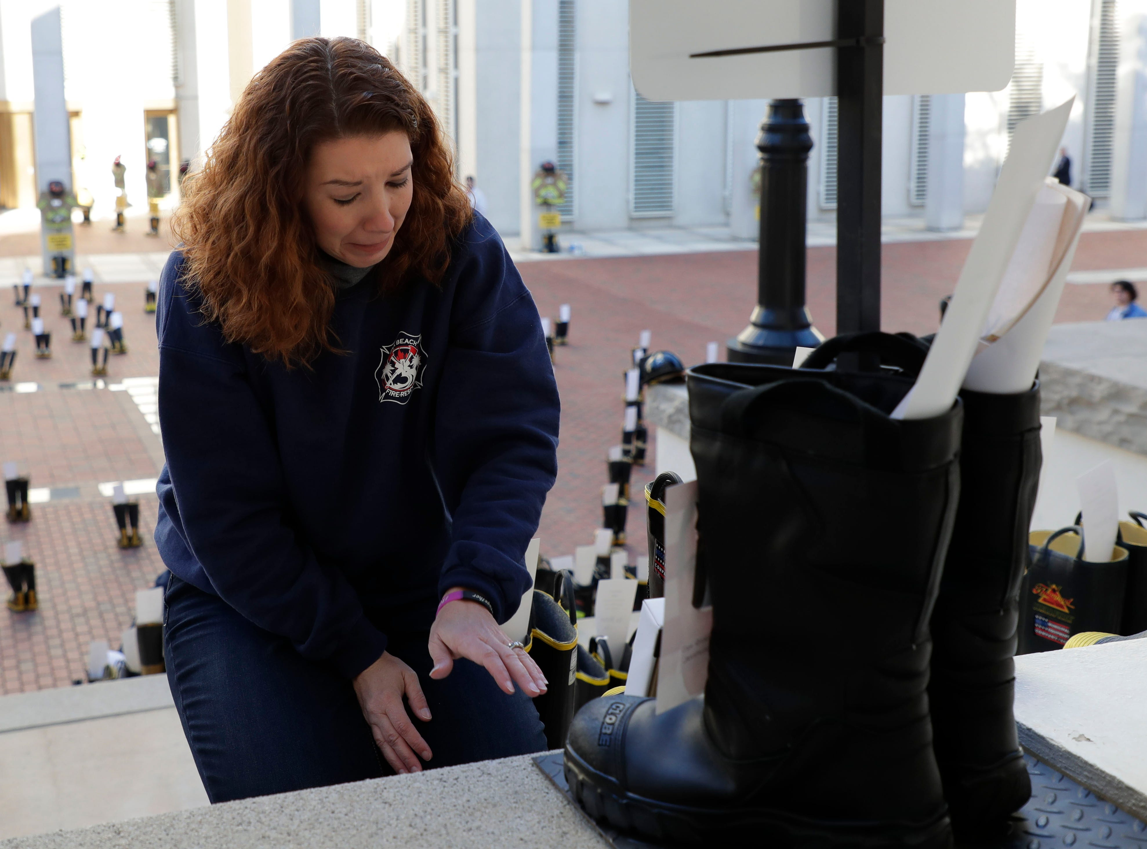 Ashley Rabon, a mother of three who lost her husband, Captain Ronald Rabon with the Jacksonville Beach Fire Department who lost his battle with appendix cancer, takes a moment of silence for her husband. Firefighters and their families from around the state create a display at the Capitol of 500 pairs of boots in honor of firefighters who lost their battle or are battling with cancer caused from smoke inhalation and carcinogens Thursday, March 7, 2019. The state of Florida is one of five states in the country that does not have a bill acknowledging cancer is a job-related illness.