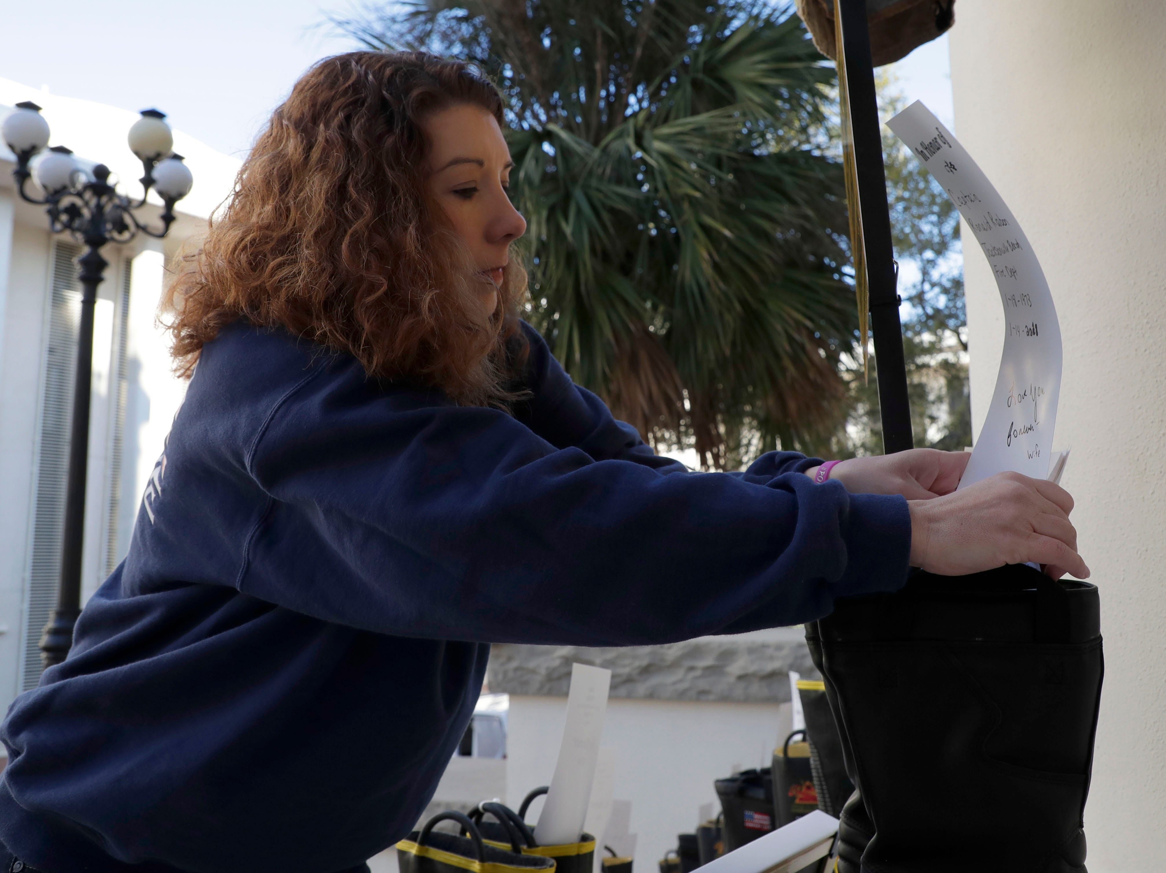 Ashley Rabon, a mother of three who lost her husband, Captain Ronald Rabon with the Jacksonville Beach Fire Department who lost his battle with appendix cancer, places a card honoring him in a pair of boots. Firefighters and their families from around the state create a display at the Capitol of 500 pairs of boots in honor of firefighters who lost their battle or are battling with cancer caused from smoke inhalation and carcinogens Thursday, March 7, 2019. The state of Florida is one of five states in the country that does not have a bill acknowledging cancer is a job-related illness.