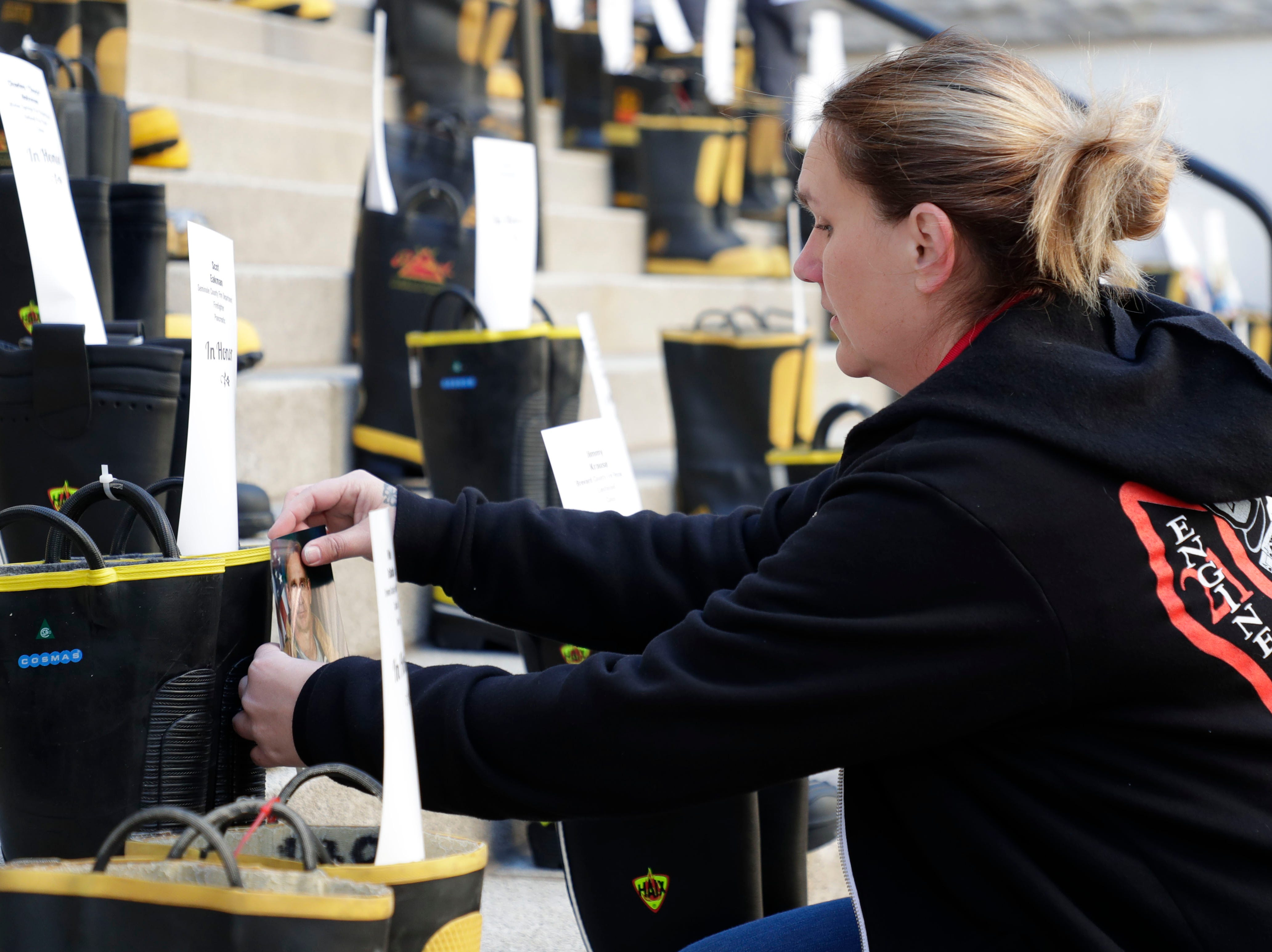 Jazz Zombo, a woman who works with Seminole County Professional Firefighters Local 3254, places a card in a boot honoring a firefighter who battled cancer. Firefighters and their families from around the state create a display at the Capitol of 500 pairs of boots in honor of firefighters who lost their battle or are battling with cancer caused from smoke inhalation and carcinogens Thursday, March 7, 2019. The state of Florida is one of five states in the country that does not have a bill acknowledging cancer is a job-related illness.