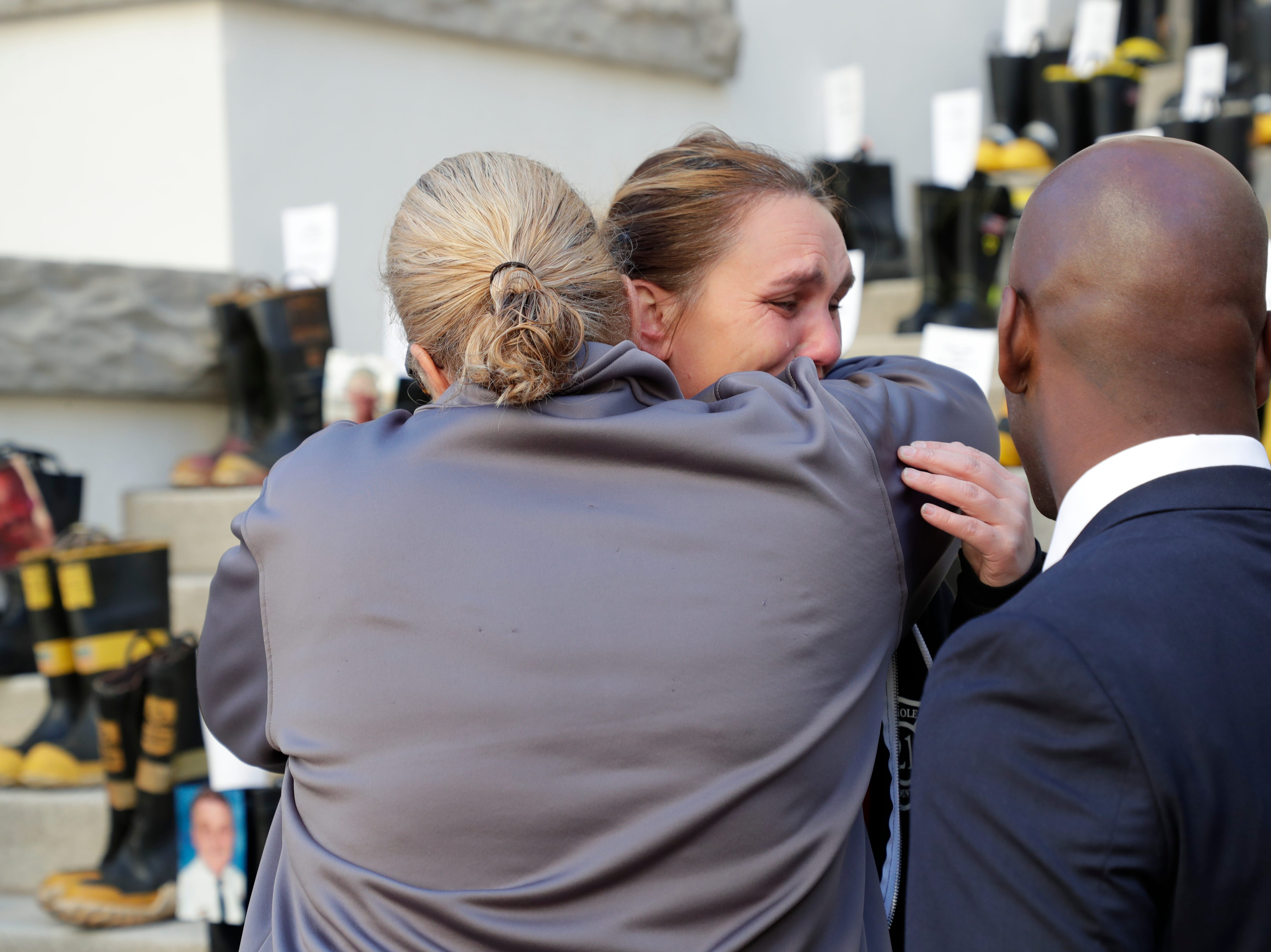 Claudine Buzzo, a firefighter with Miami-Dade Local 1403, left, hugs Jazz Zombo, a firefighter with Seminole County Professional Firefighters Local 3254, as she cries after placing a photo of a firefighter who lost their battle with cancer. Firefighters and their families from around the state create a display at the Capitol of 500 pairs of boots in honor of firefighters who lost their battle or are battling with cancer caused from smoke inhalation and carcinogens Thursday, March 7, 2019. The state of Florida is one of five states in the country that does not have a bill acknowledging cancer is a job-related illness.