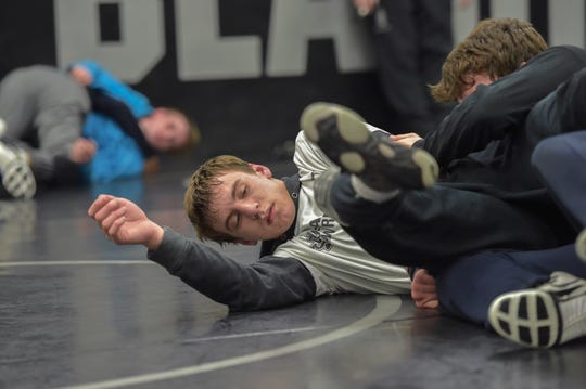 "Jensen Beach High School wrestler Wyatt Kirkhan, 17 (center), wrestles with Hayden Zehe (right) 18, during a team practice on Wednesday, March 6, 2019, inside the school's wrestling room in Jensen Beach. ""The hardest worker is going to win,"" Kirkhan said. ""It's just you and someone else on the mat, and you don't have any excuses."" Kirkhan and teammate Dylan Layton are expected to contend for a state championship this weekend at the Silver Spurs Area in Kissimmee."