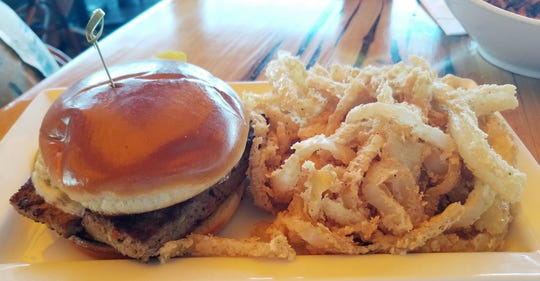 Fred's Incredible Meatloaf Sandwich is a slice of seared meatloaf topped with fried onion straws, provolone cheese, and horseradish sauce on a toasted brioche bun.