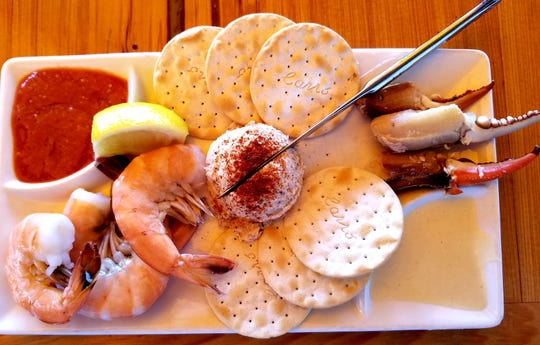 The seafood sampler included steamed shrimp, smoked dolphin dip, and crab claws garnished with water crackers,  cocktail and horseradish sauces.