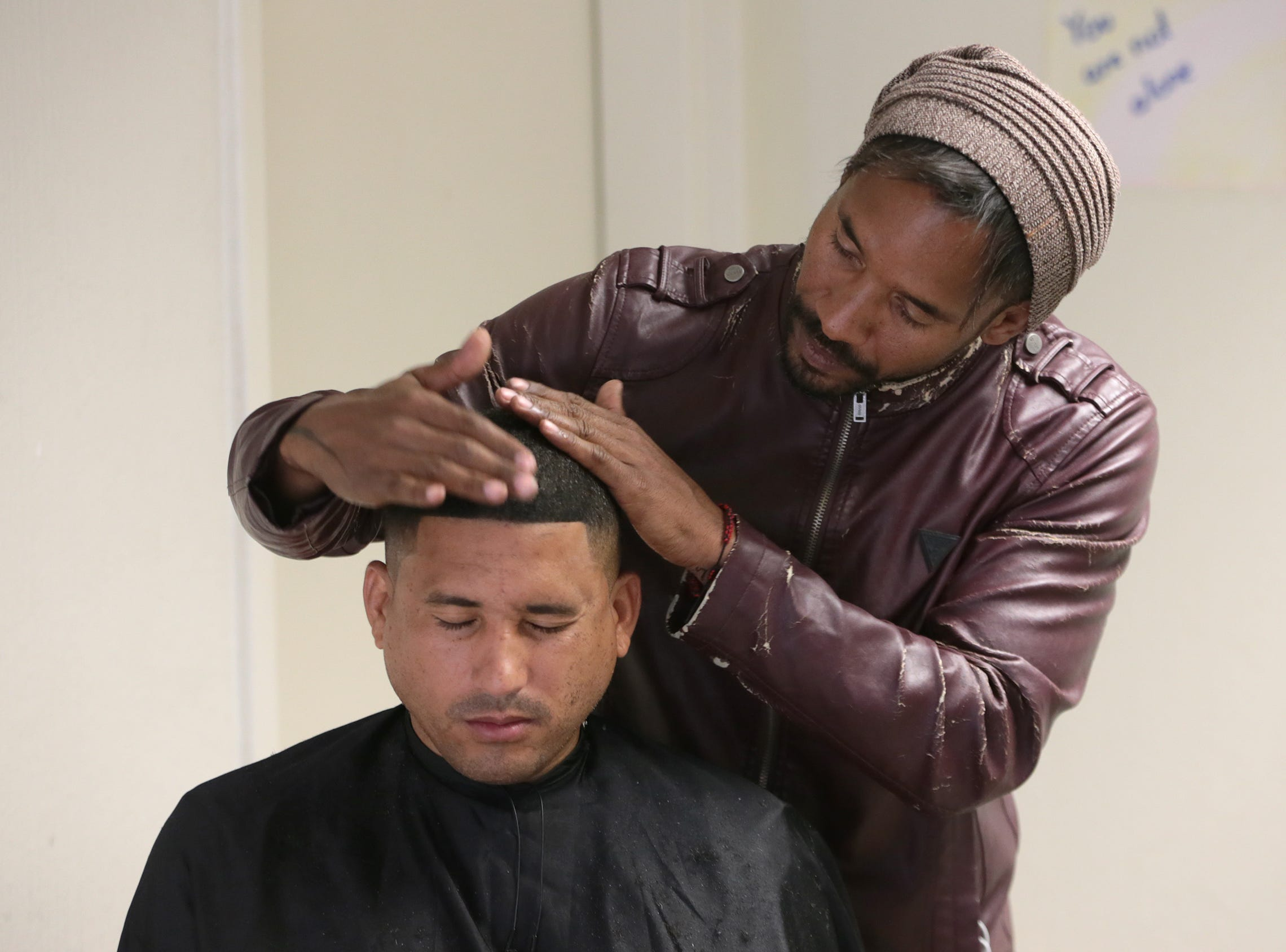 Cuban migrant Osiris, a barber by trade, cuts hair of his fellow Cubans as he awaits entry into the United States. Over 250 Cuban migrants, among others, are sheltering at the Colegio de Bachilleres in Juarez as they await their number to be called.