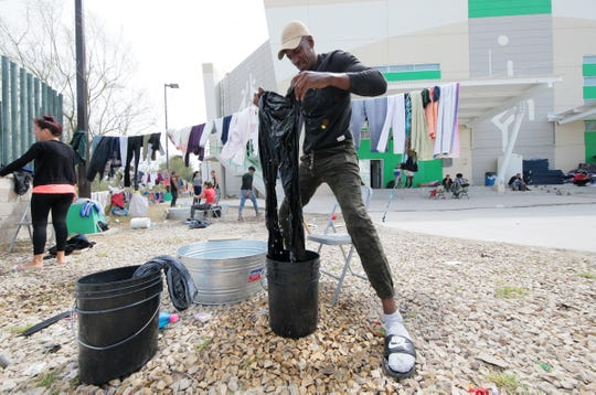 Cuban migrant Carlo Arencibia washes his clothing in a bucket outside the shelter at the Colegio de Bachilleres in Juárez. Over 250 Cuban migrants and countless Central Americans are waiting in Juárez for their turn to make their asylum pleas in the U.S.