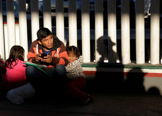 In this Jan. 25, 2019, file photo, a migrant who did not give his name looks on with his children as they wait to hear if their number is called to apply for asylum in the United States, at the border in Tijuana, Mexico. The Trump administration's effort to make asylum seekers wait in Mexico explicitly targets Spanish-speakers and people from Latin America, according to internal guidelines of a highly touted strategy to address the burgeoning number of Central Americans arriving at U.S. borders.