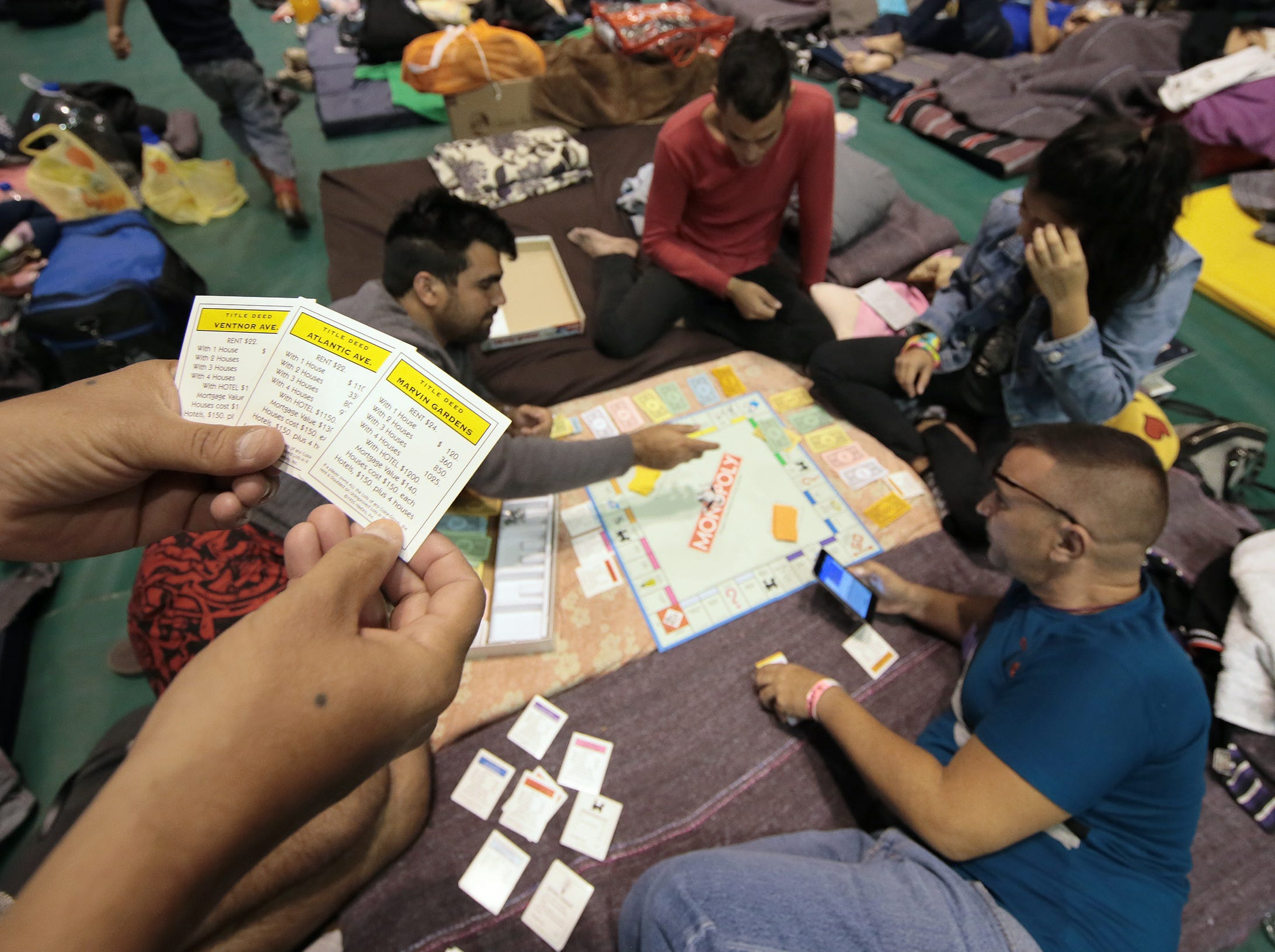 A group of Cuban migrants play Monopoly at a shelter in Juarez.