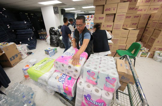Shelter workers organize supplies at the migrant shelter at the Colegio de Bachilleres in Juarez.