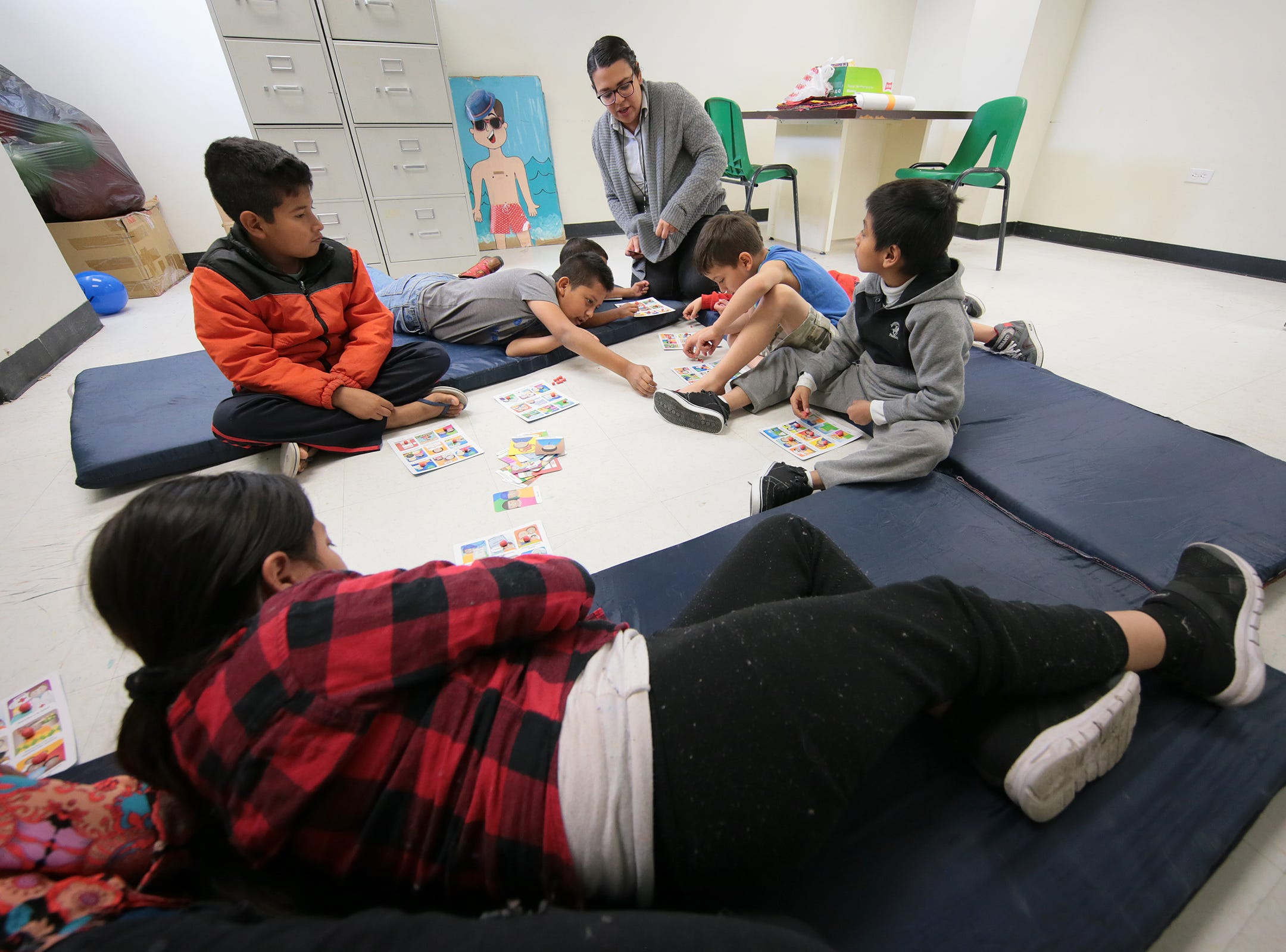 Child counselor Karen Serrano works with migrant children in a shelter in Juarez. Migrant families are waiting at the Colegio de Bachilleres in Juarez for their assigned number to be called to cross the border.