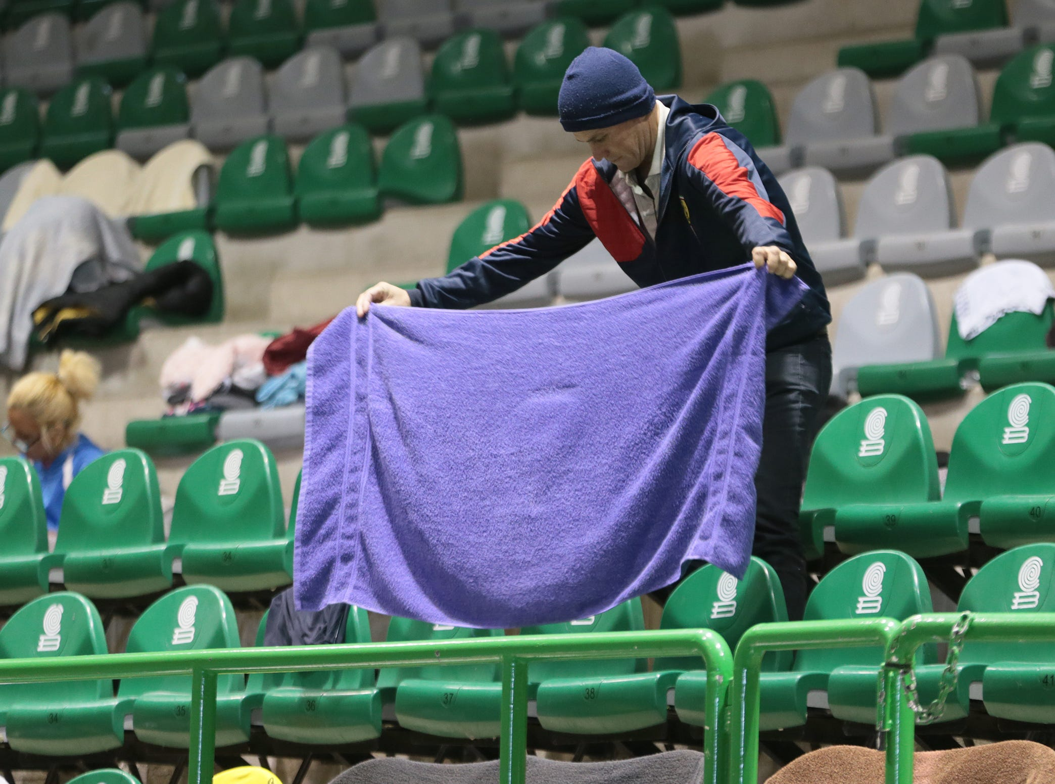 A Cuban migrant hangs his towel over the seating in the gym at Colegio de Bachilleres in Juarez.