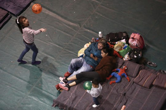 In this Feb. 19, 2019, file photo, migrants who are awaiting their chance to request asylum in the U.S. pass the time inside a shelter in Bachilleres gymnasium in Juárez, Mexico. The Trump administration's effort to make asylum seekers wait in Mexico explicitly targets Spanish-speakers and people from Latin America, according to internal guidelines of a highly touted strategy to address the burgeoning number of Central Americans arriving at U.S. borders.