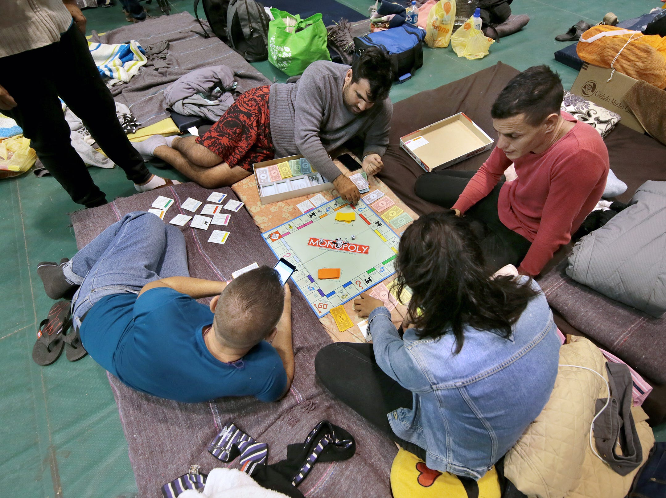 Cuban migrants play Monopoly on Thursday, March 7, 2019, at a shelter in Juárez.
