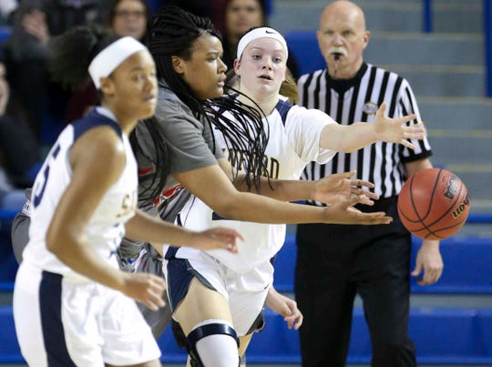 Conrad's Ja'Nylah Whittlesey (second from left) grabs at the ball as Sanford's Allie Kubek (right) moves in during the second half of Sanford's 52-41 win in a DIAA state tournament semifinal at the Bob Carpenter Center.