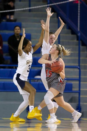 Sanford's Kanisa Tucker (left) and Allie Kubek defend as Conrad's Jordan Rook moves to the basket in the first half of a DIAA state tournament semifinal at the Bob Carpenter Center Wednesday.