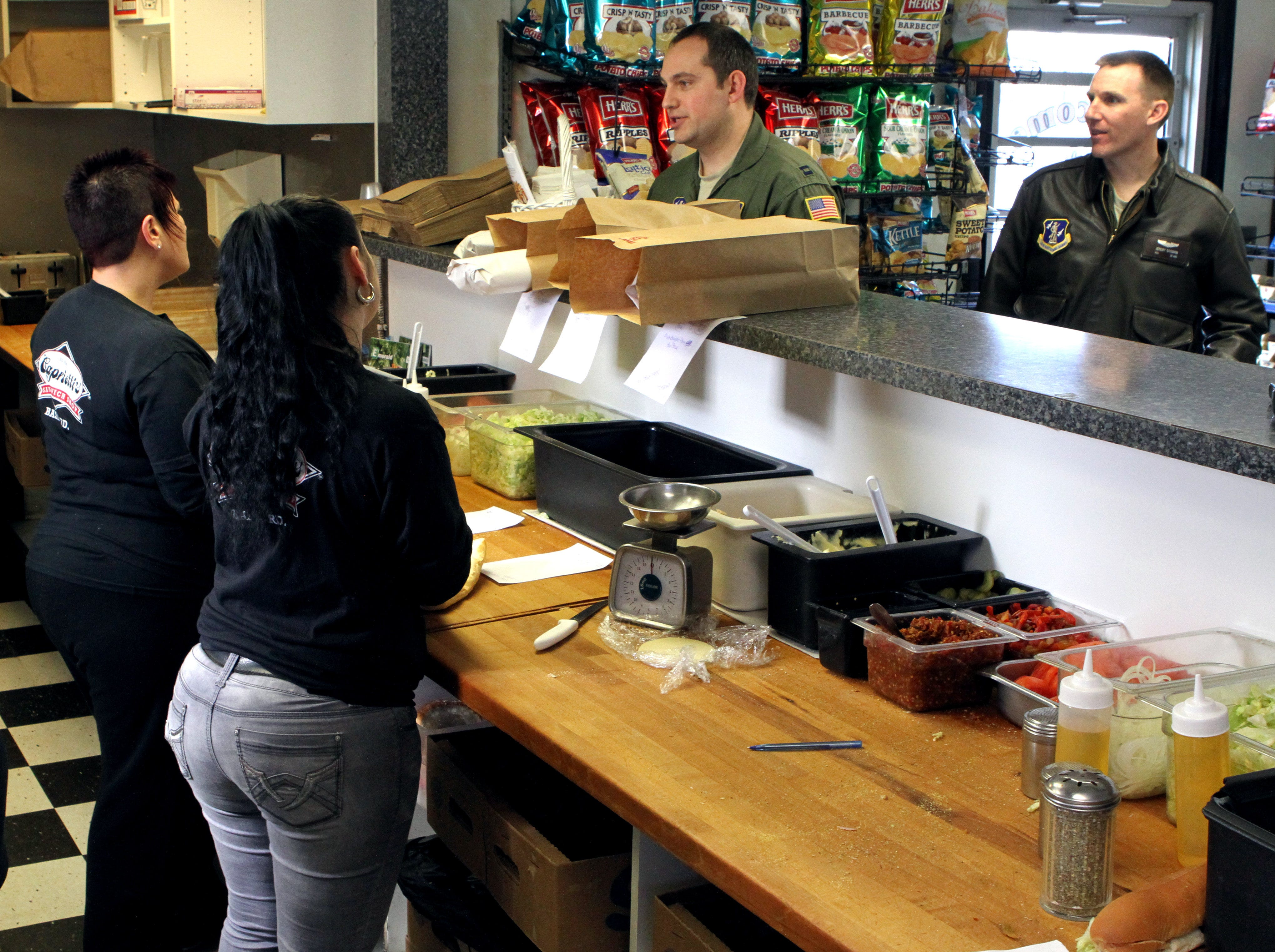 Capt. Zac Balas (left) and Maj. Jeremy Goodwin (right) wait for their sandwiches to be made at Capriotti's on Basin Road near New Castle in 2013.