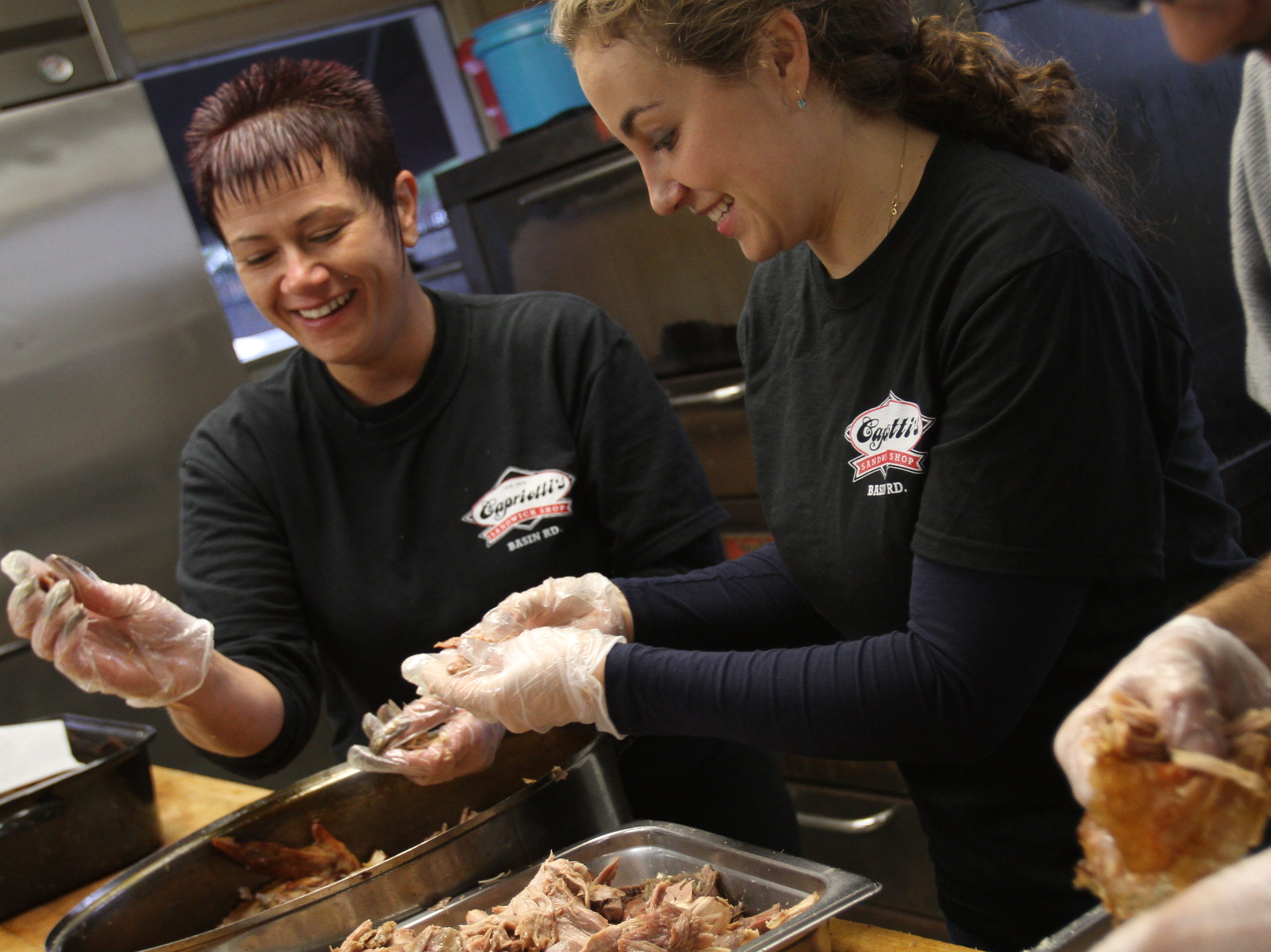 Emily Dominick (left) helps former News Journal reporter Ashley Barnas as she breaks down a turkey in 2012.