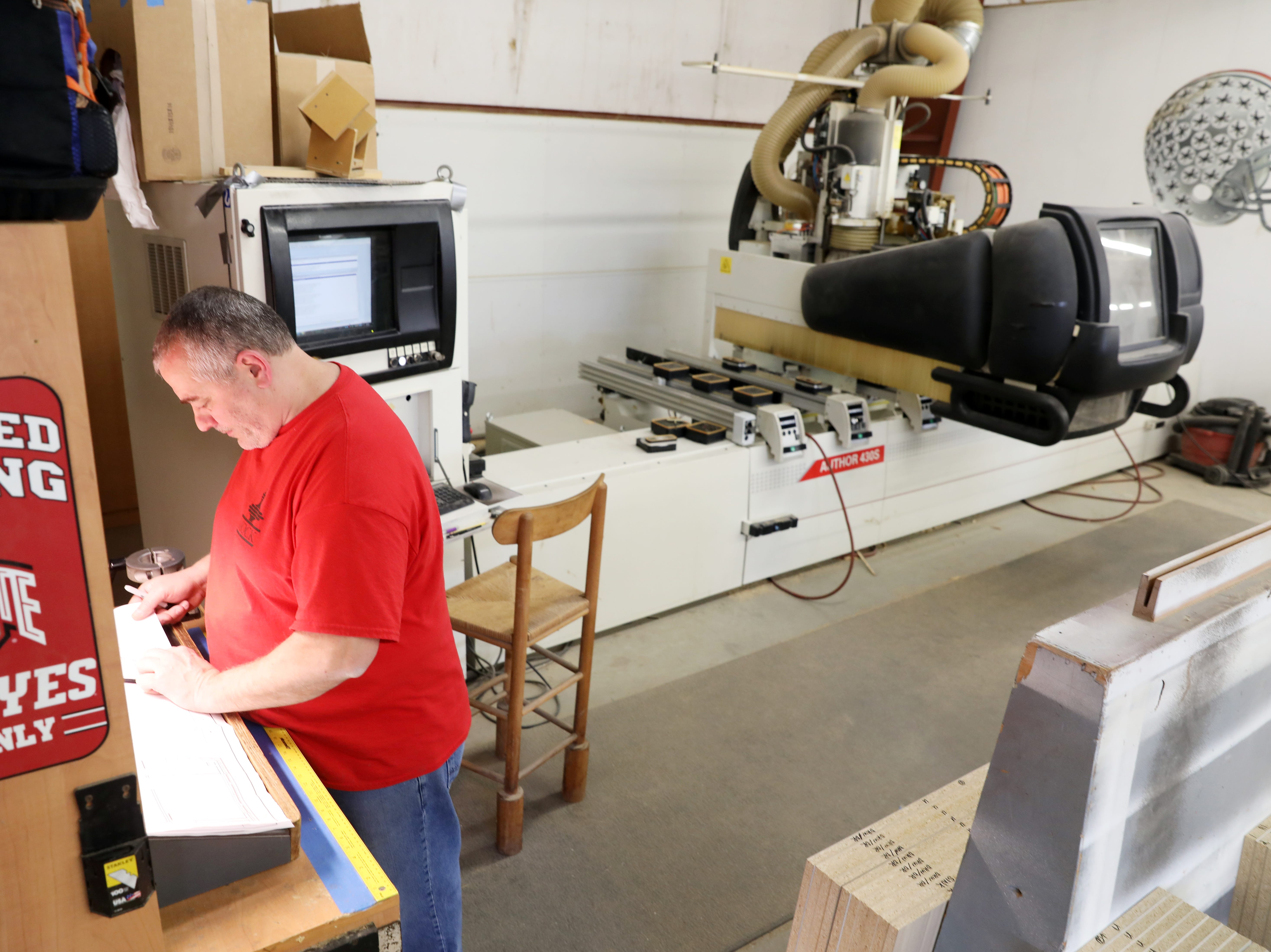 Tim Love looks at plans at a CNC machine at Mock Woodworking.