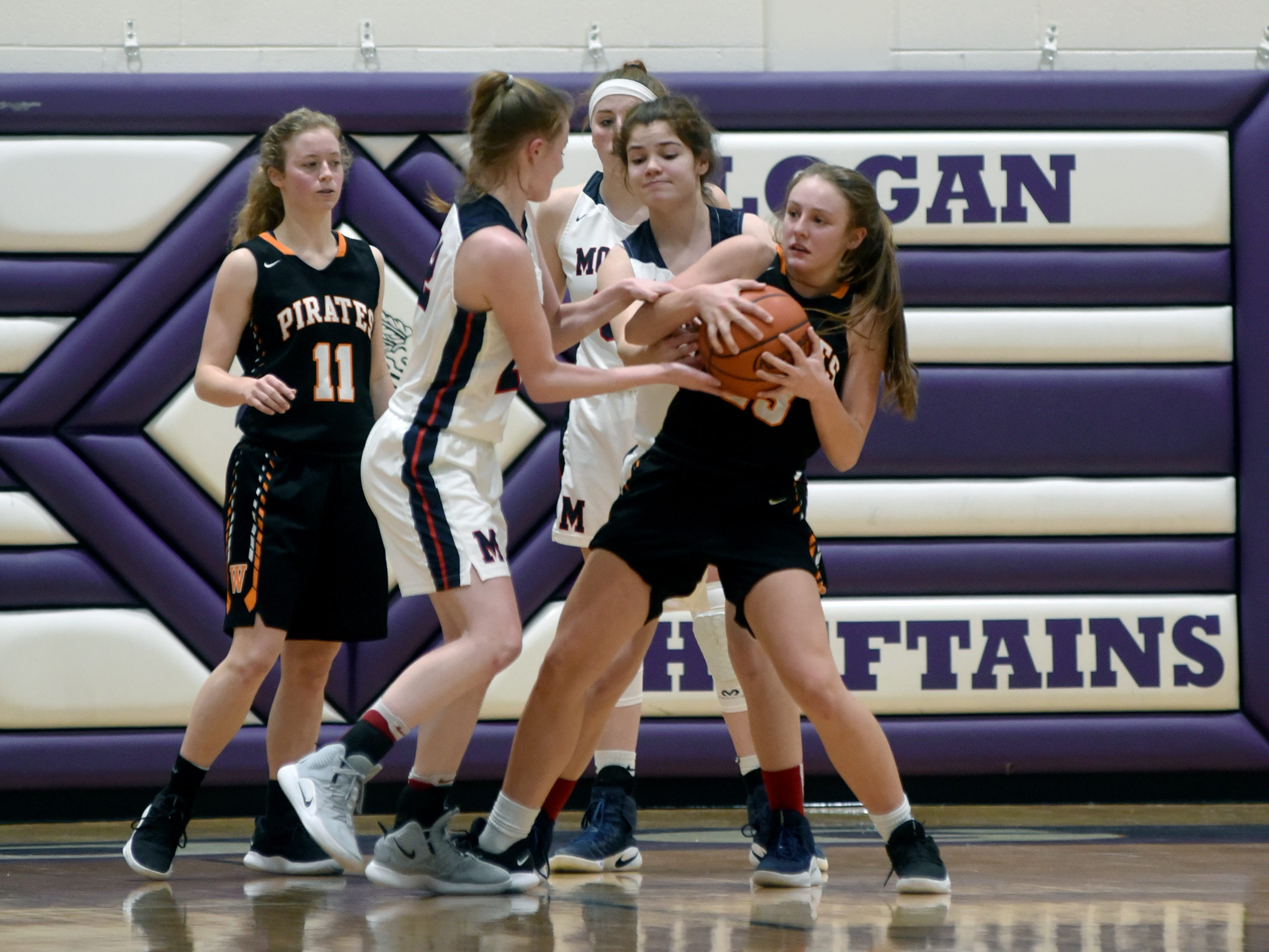 Sophia Smith, left, and Katie Hook tie up Kaylee Darnell during Morgan's 56-55 loss to Wheelersburg in a Division III regional semifinal at Logan.