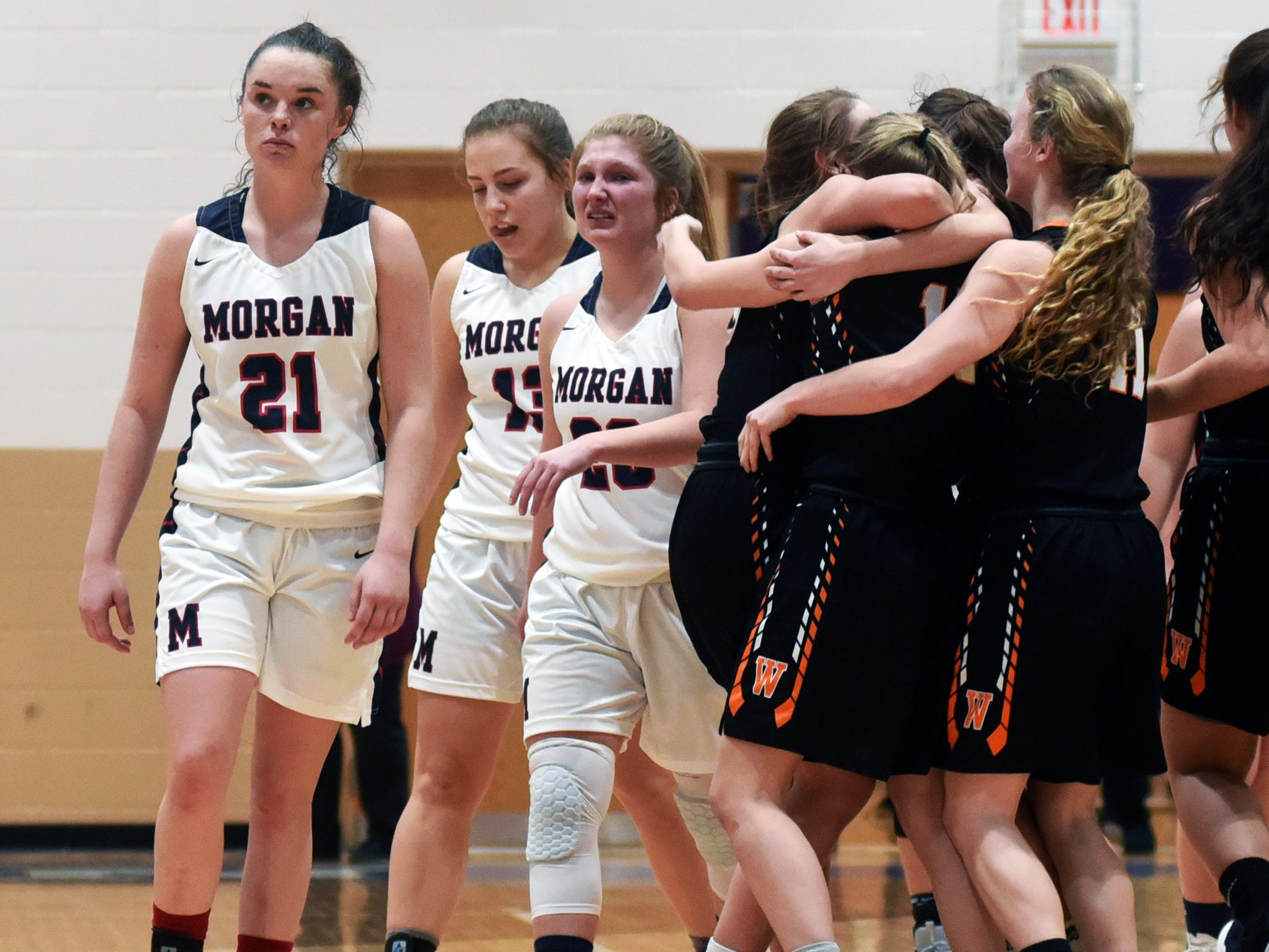 Morgan's Kaylie Apperson, left, Riley Coon and Kara Hopkins walk off the floor following a 56-55 loss to Wheelersburg in a Division III regional semifinal at Logan.