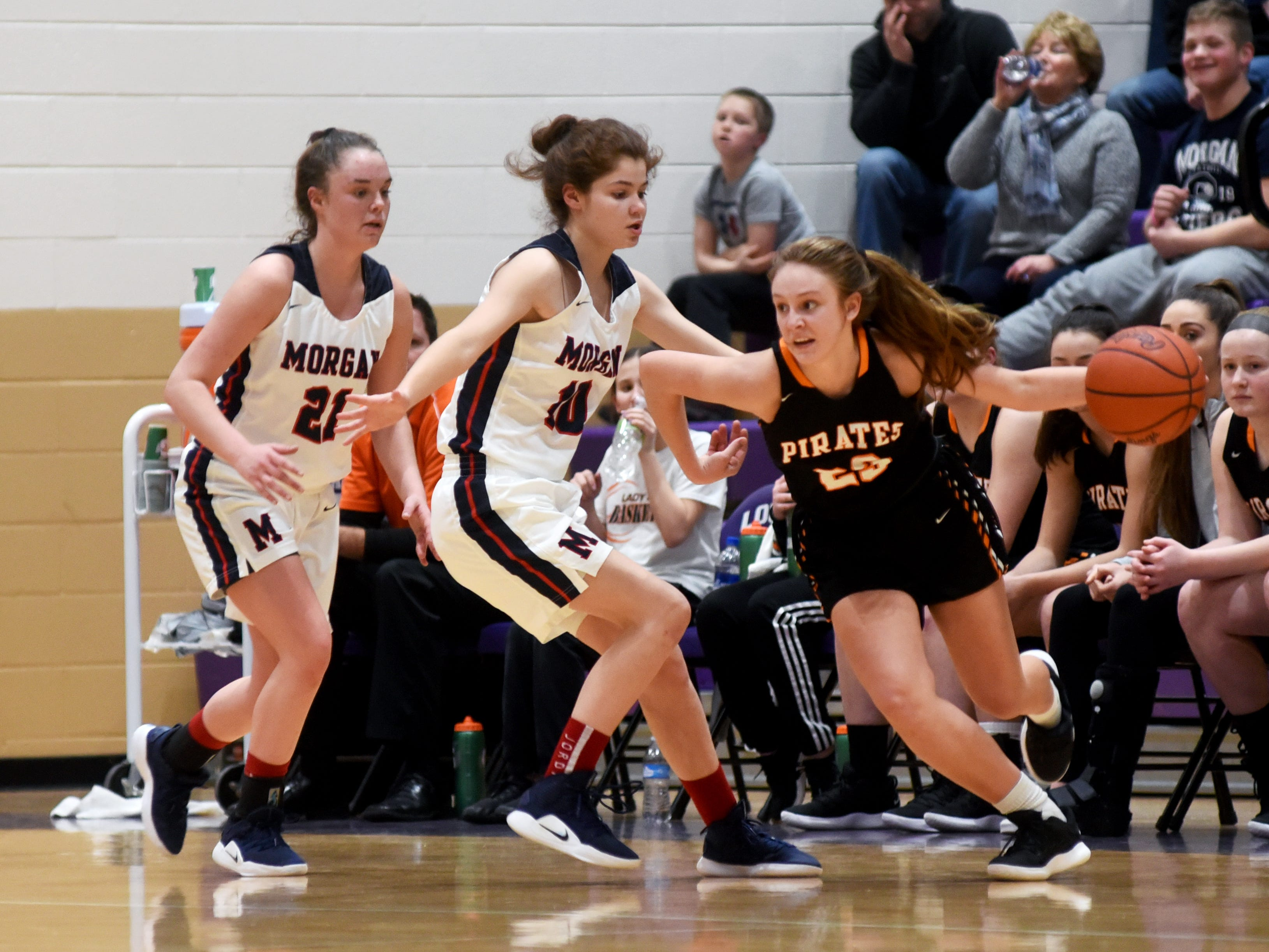 Kaylee Darnell tries to drive around Morgan's Kaylie Apperson, left, and Katie Hook during Wheelersburg's 56-55 win in a Division III regional semifinal at Logan.