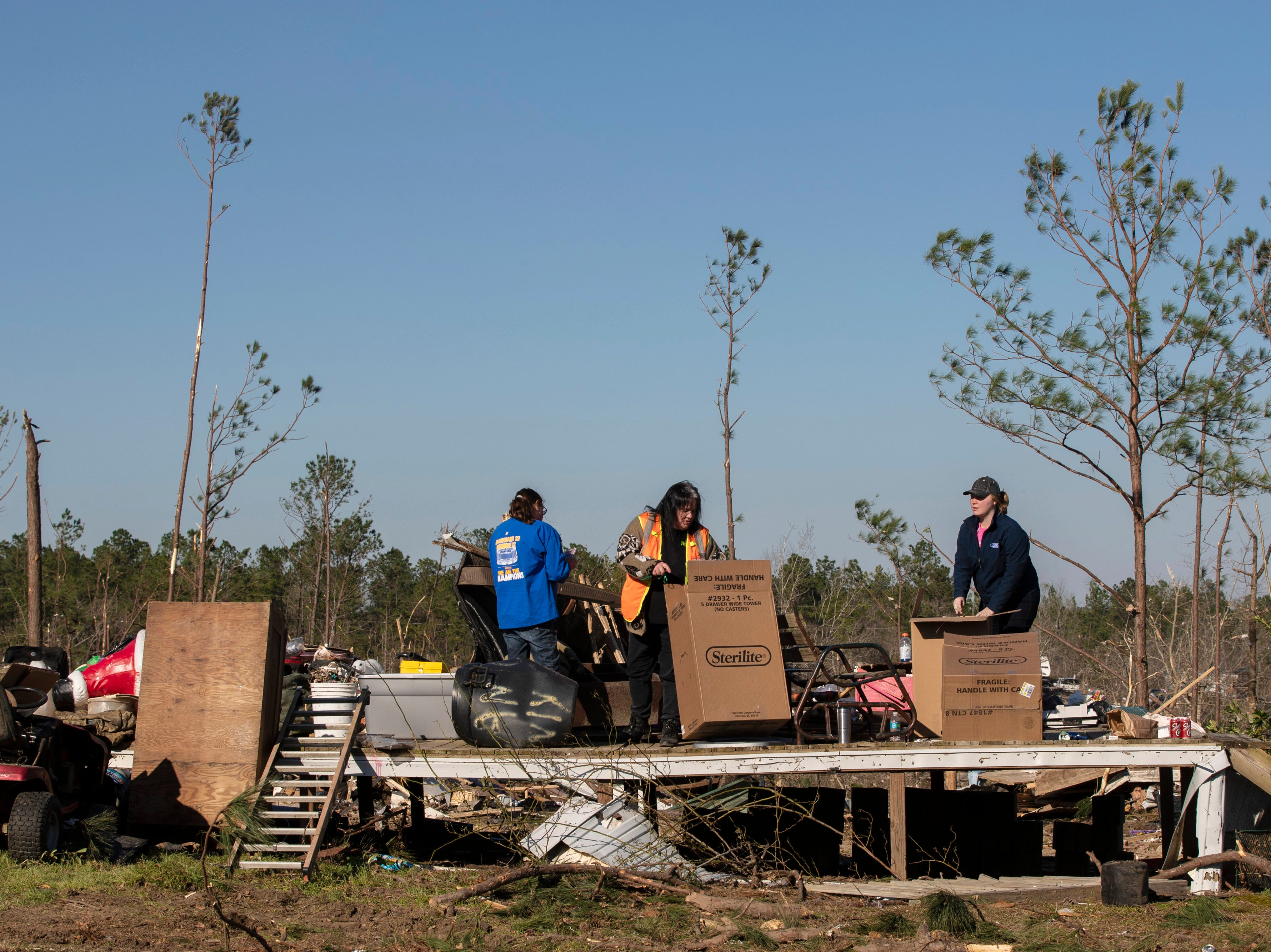 Susanne Polk, center, gathers what is left of her items where her home once stood in Beauregard, Ala. on March 6, 2019.