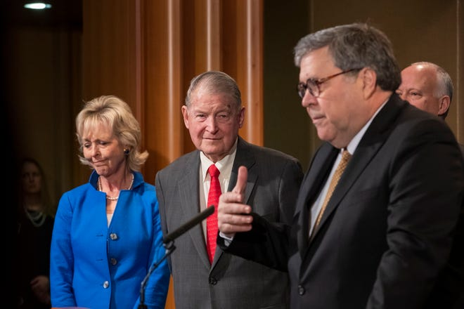 Former FBI Director William Webster, center, and his wife Lynda listen to Attorney General William Barr during a news conference at the Department of Justice in Washington.