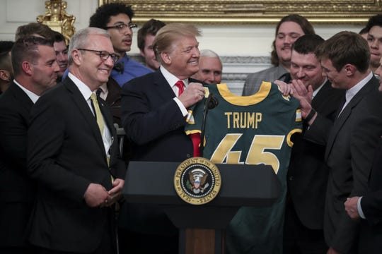 President Donald Trump receives a football jersey with his name on it from quarterback Easton Stick (R) as he welcomes the Football Championship Subdivision champion North Dakota State Bison in the Diplomatic Room of the White House.
