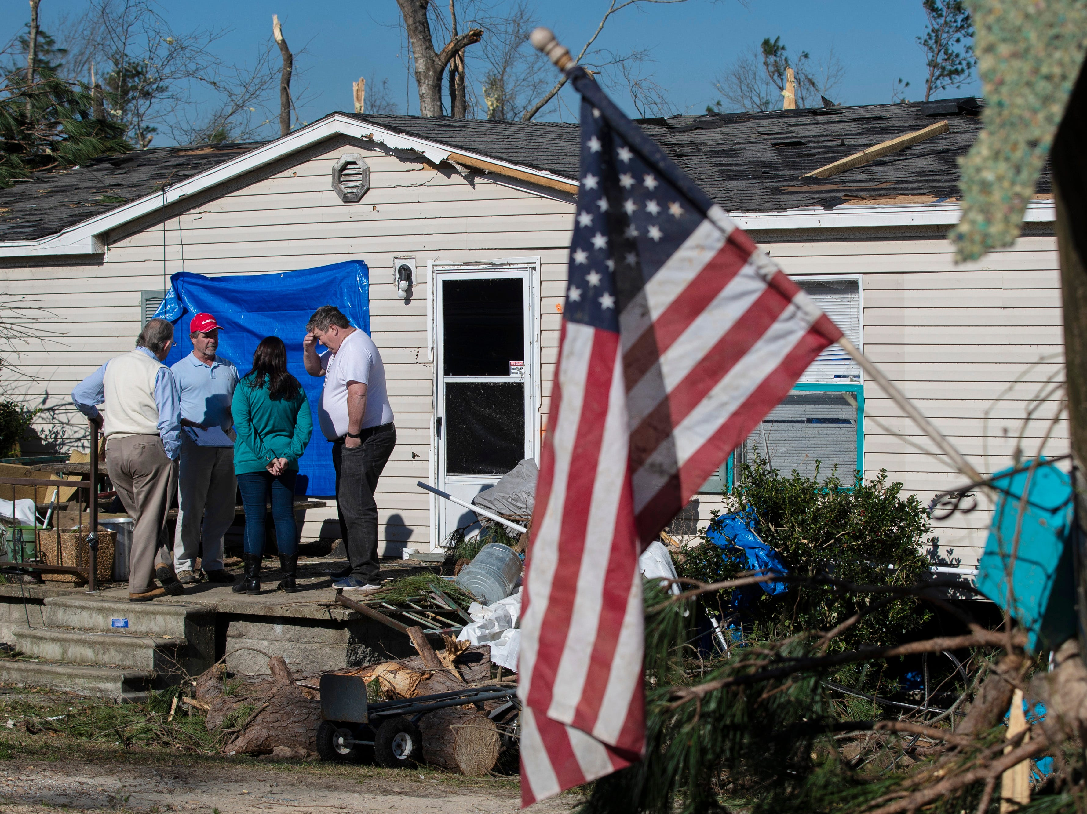 Richard Widger, right, and Sondra Widger talk with their insurance agent as they deal with the damage to their home in Beauregard, Ala. on March 6, 2019.